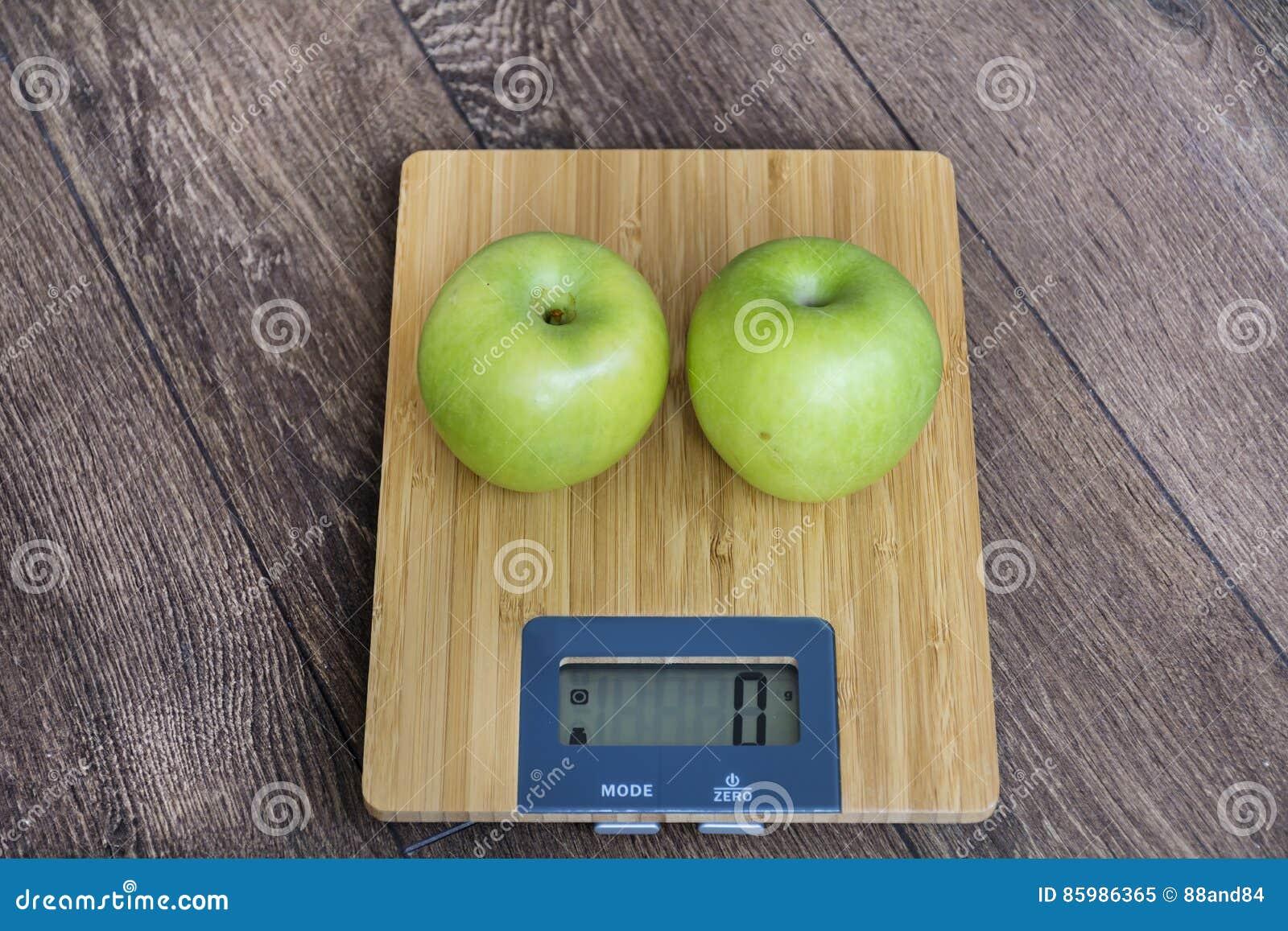 Groene appelen op keukenschaal