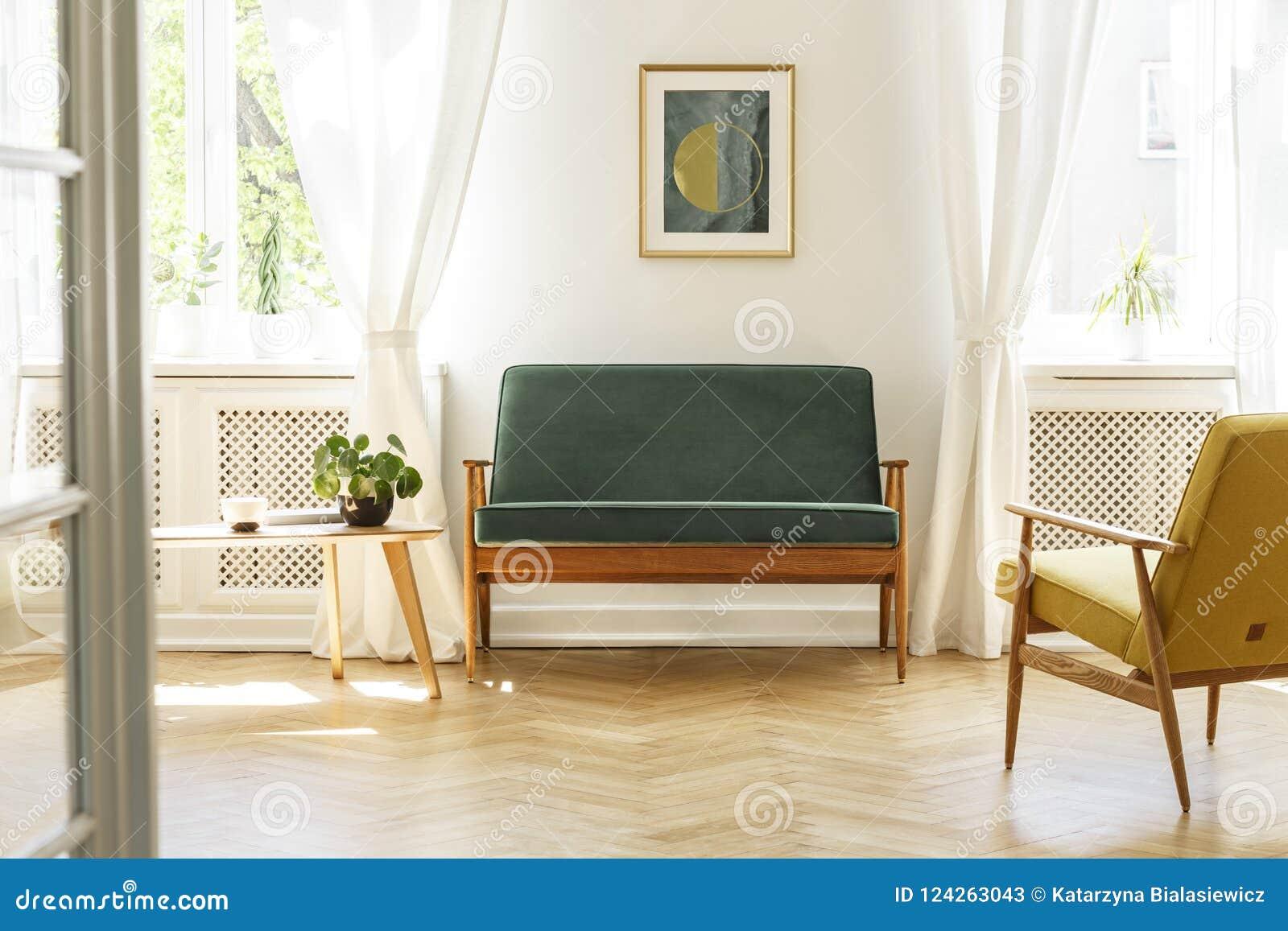 Groene bank met donker, houten kader en een gele leunstoel op z n gemak i