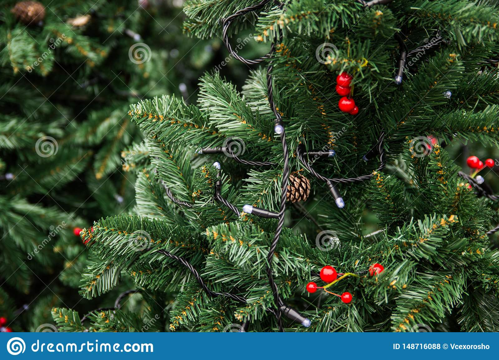 Groene boom die met lichten, kegels en rode bessen wordt verfraaid