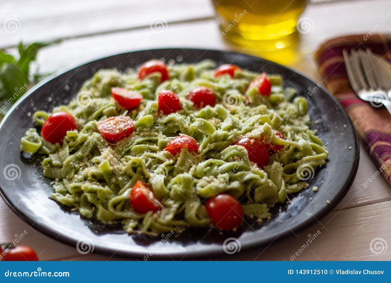 Groene deegwaren met tomaten en parmezaanse kaaskaas Witte achtergrond