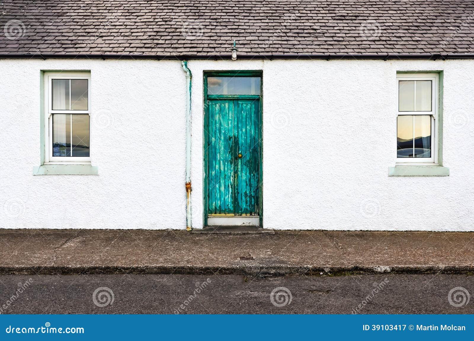 Groene deur en twee vensters op wit muurhuis