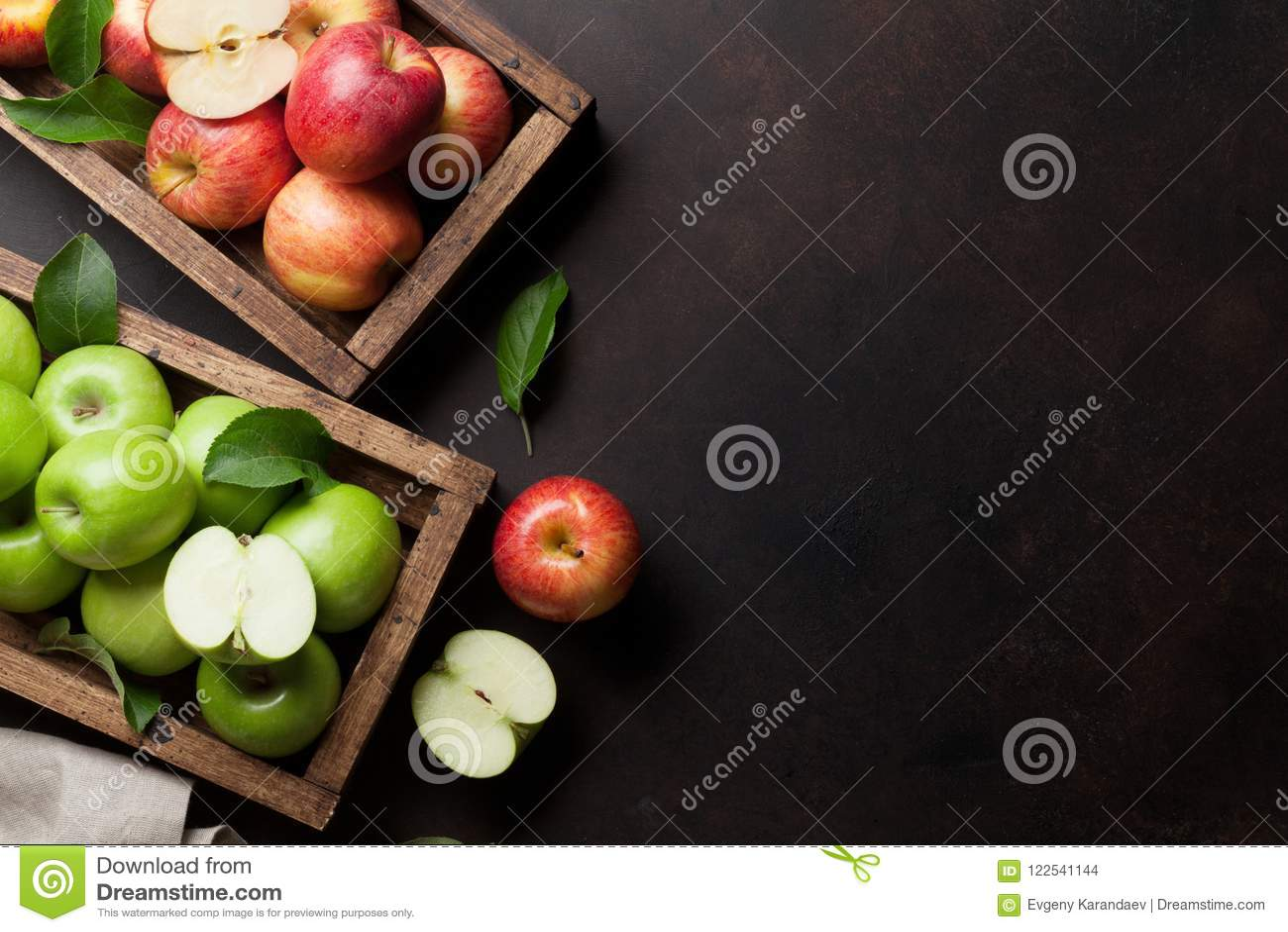 Groene en rode appelen in houten doos