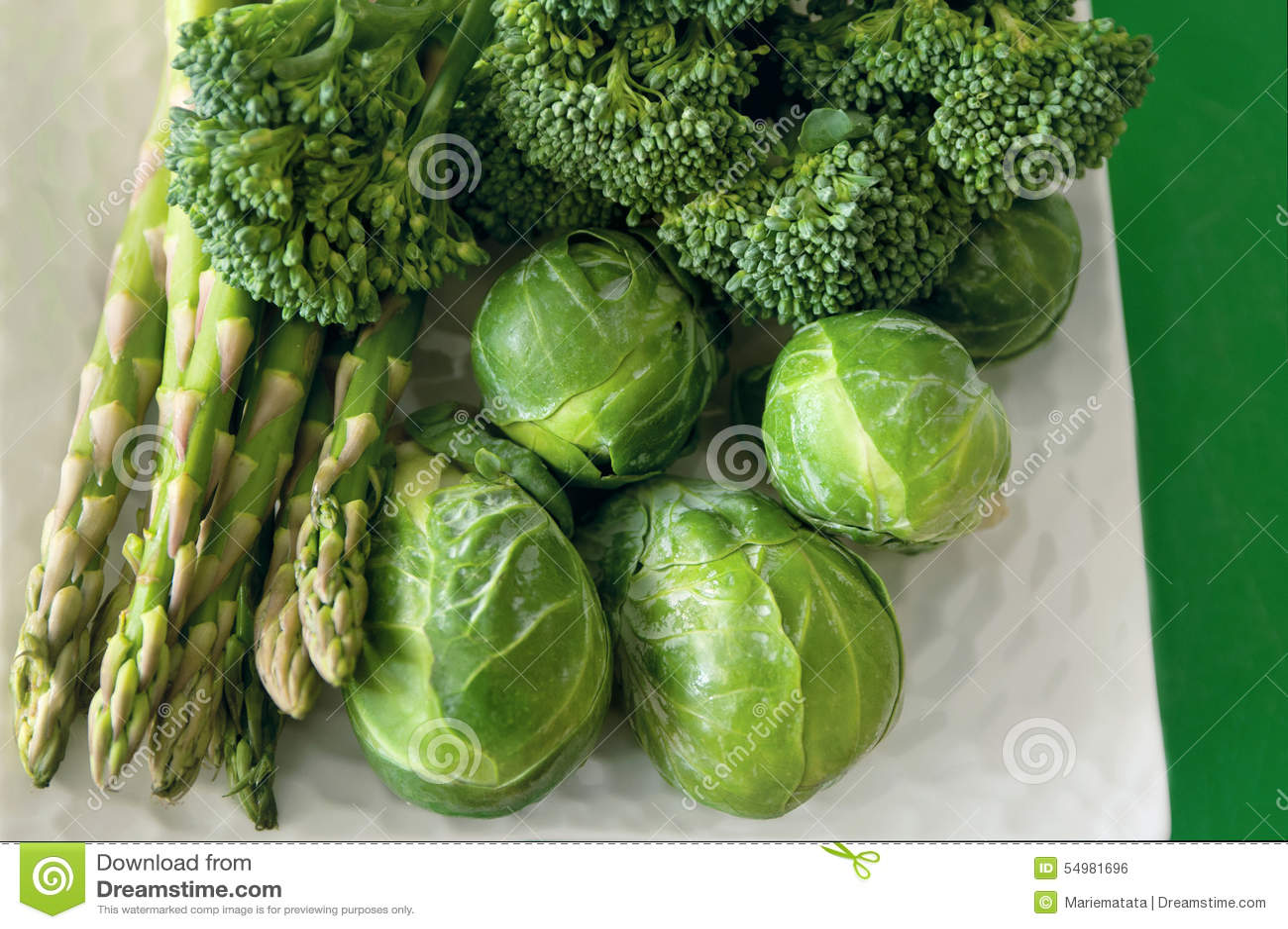 Groene groenten op witte plaat