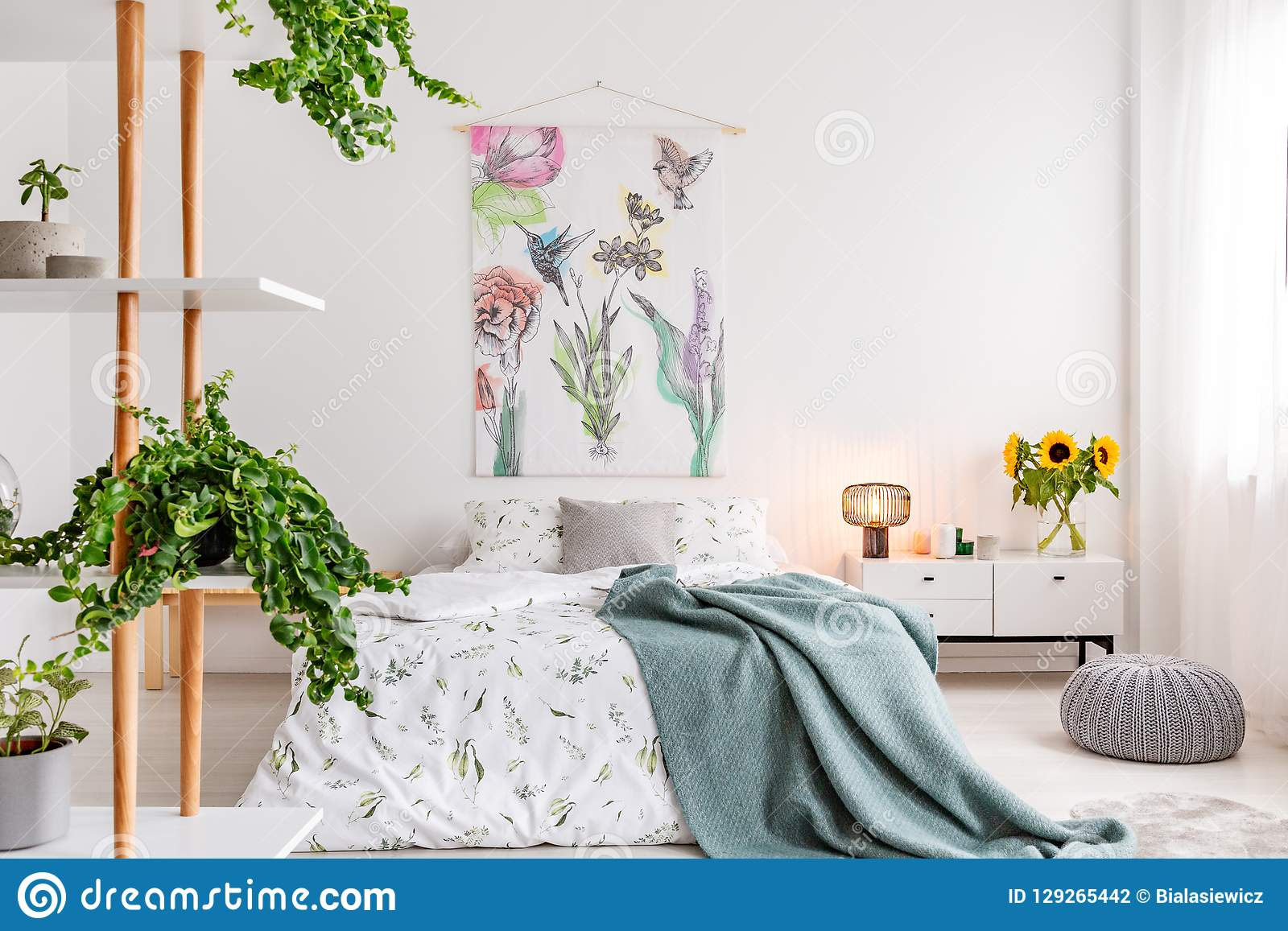Groene installaties op planken naast een bed gekleed in wit katoenen beddegoed en wintertalings blauwe deken in een helder slaapk