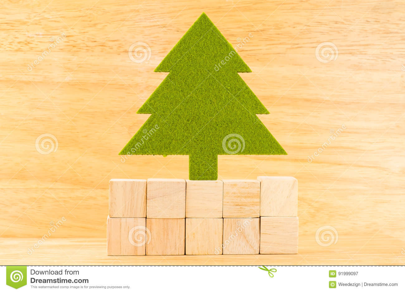 Groene Kerstmisboom op groep houten kubusblok in houten ruimte,