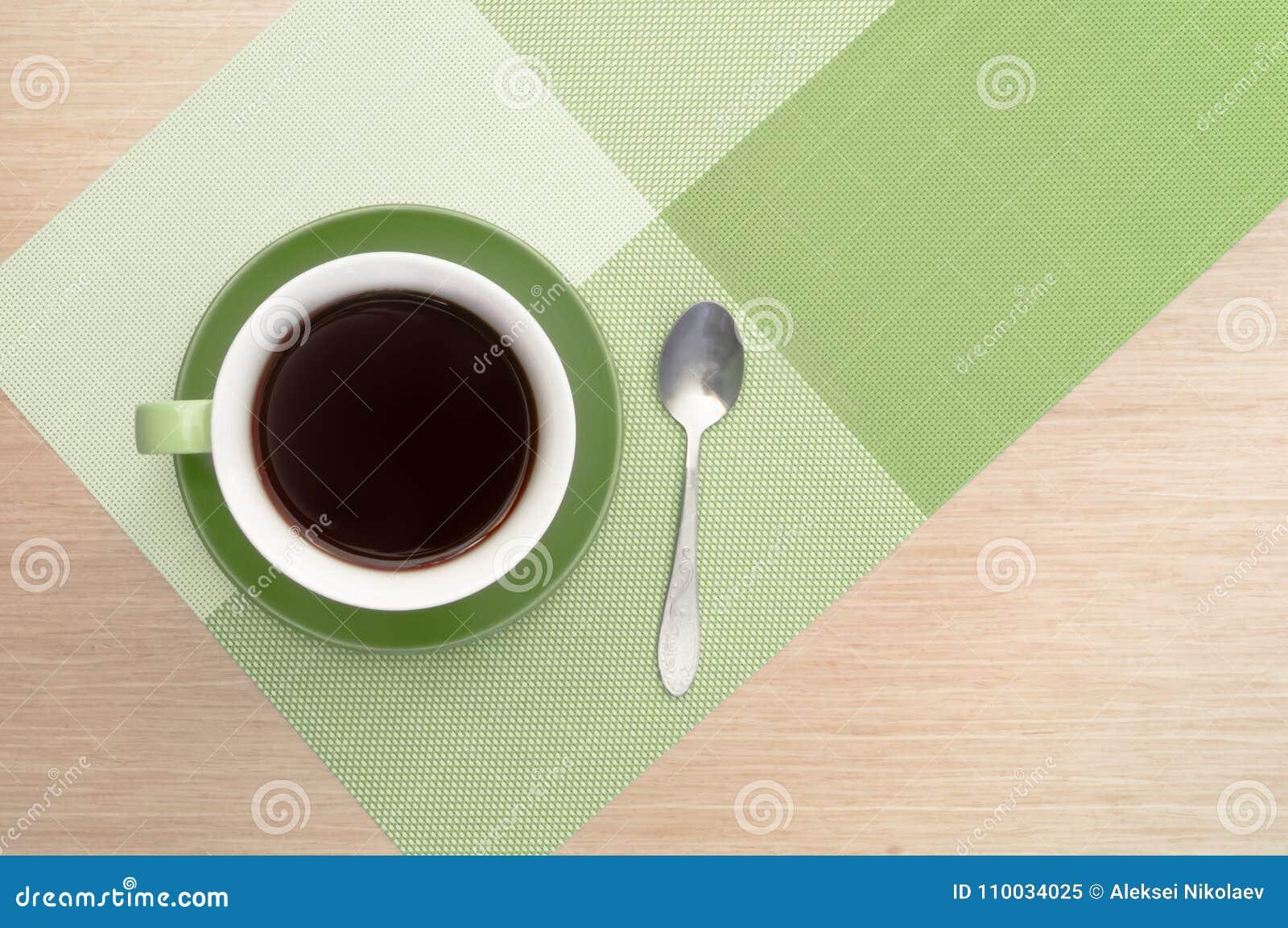 Groene kop van koffie op de lijstachtergrond en het tafelkleed en en lepel