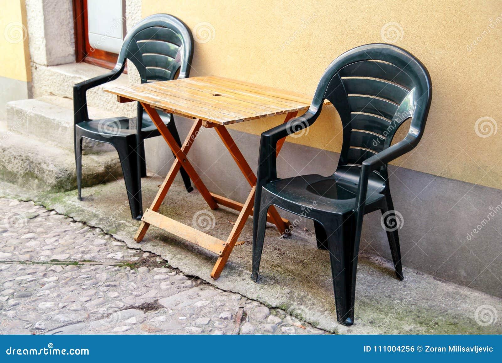 Groene plastic stoelen en houten lijst openlucht voor huis op