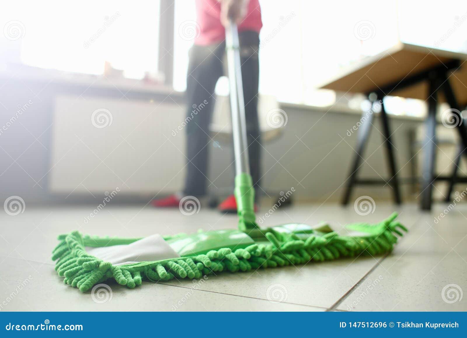 Groene plastic zwabber die gelamineerde lichte vuile vloer schoonmaken