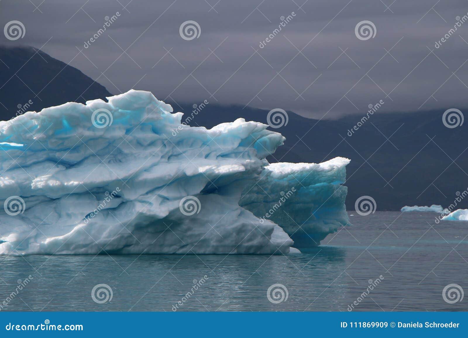Groenland, blauwe ijsberg met lichtblauwe vlekken binnen van het andwith dramatische stemming van de hemel in de Atlantische Ocea
