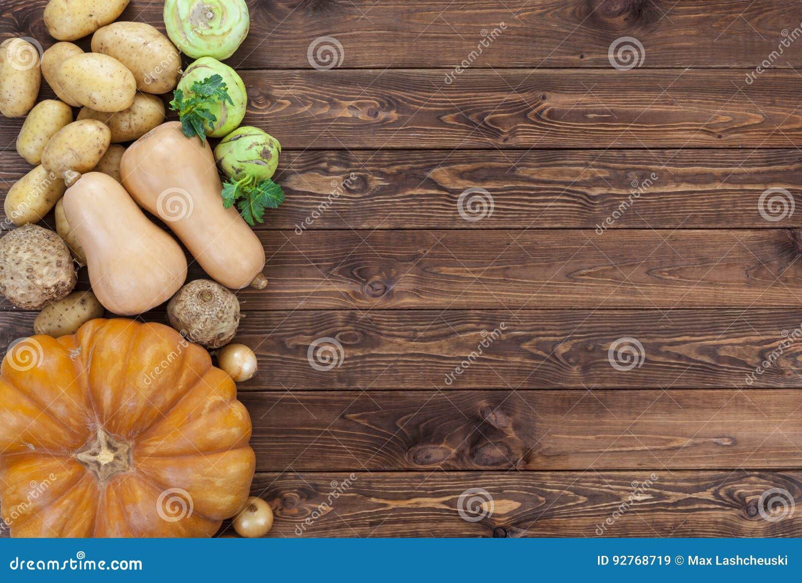 Groenten op houten achtergrond Pompoen, courgette, aardappels, uien en andere groenten, hoogste mening, exemplaarruimte