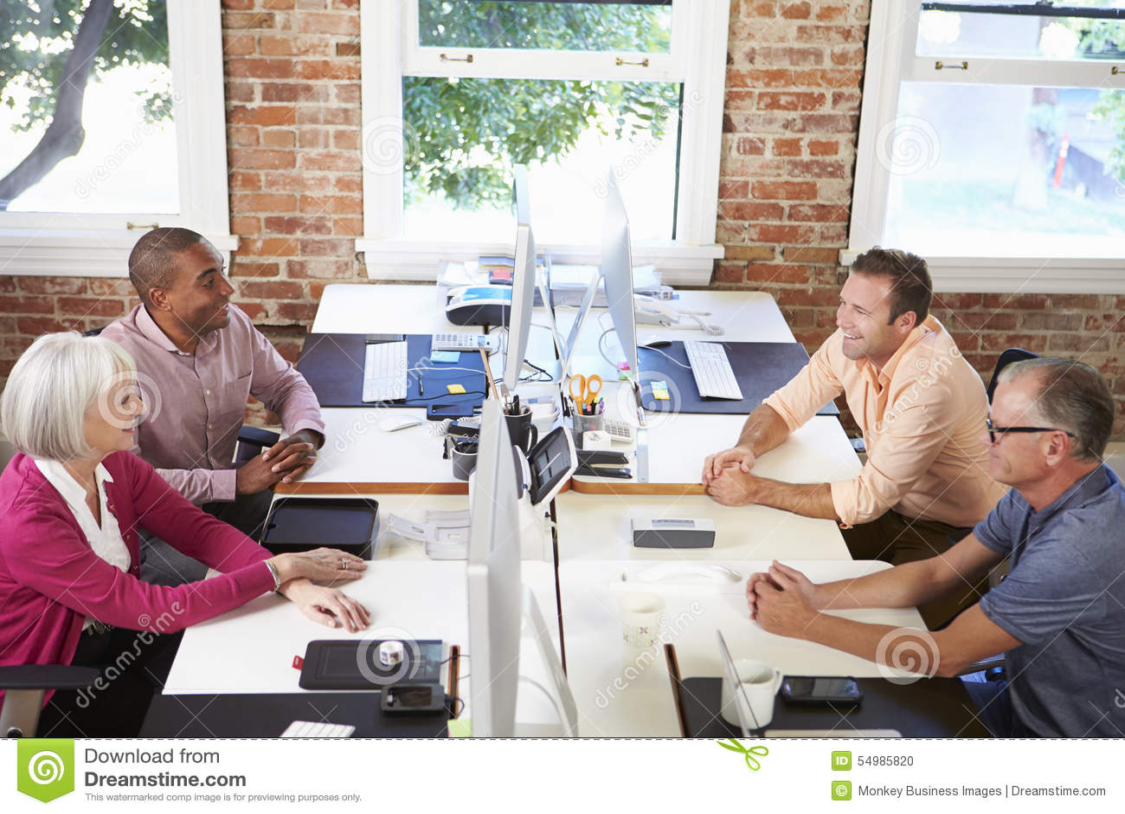 Groep Arbeiders bij Bureaus in Modern Ontwerpbureau