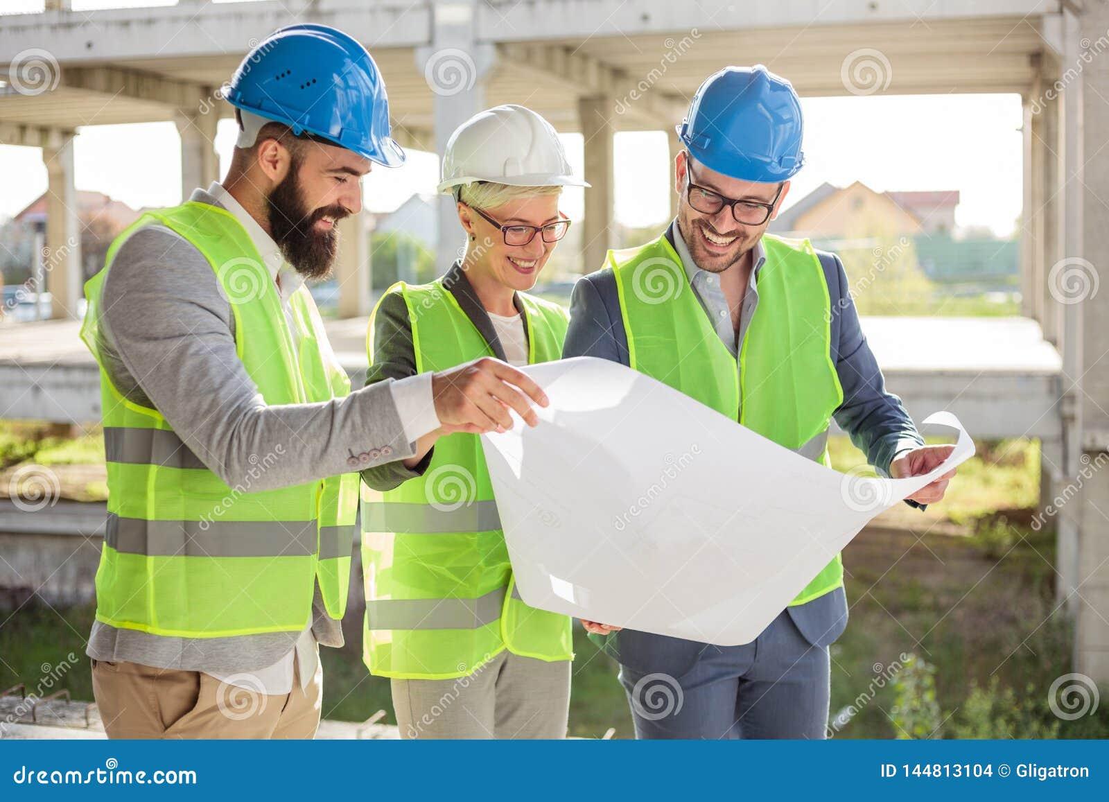 Groep architecten of partners die plattegronden op een bouwwerf bespreken
