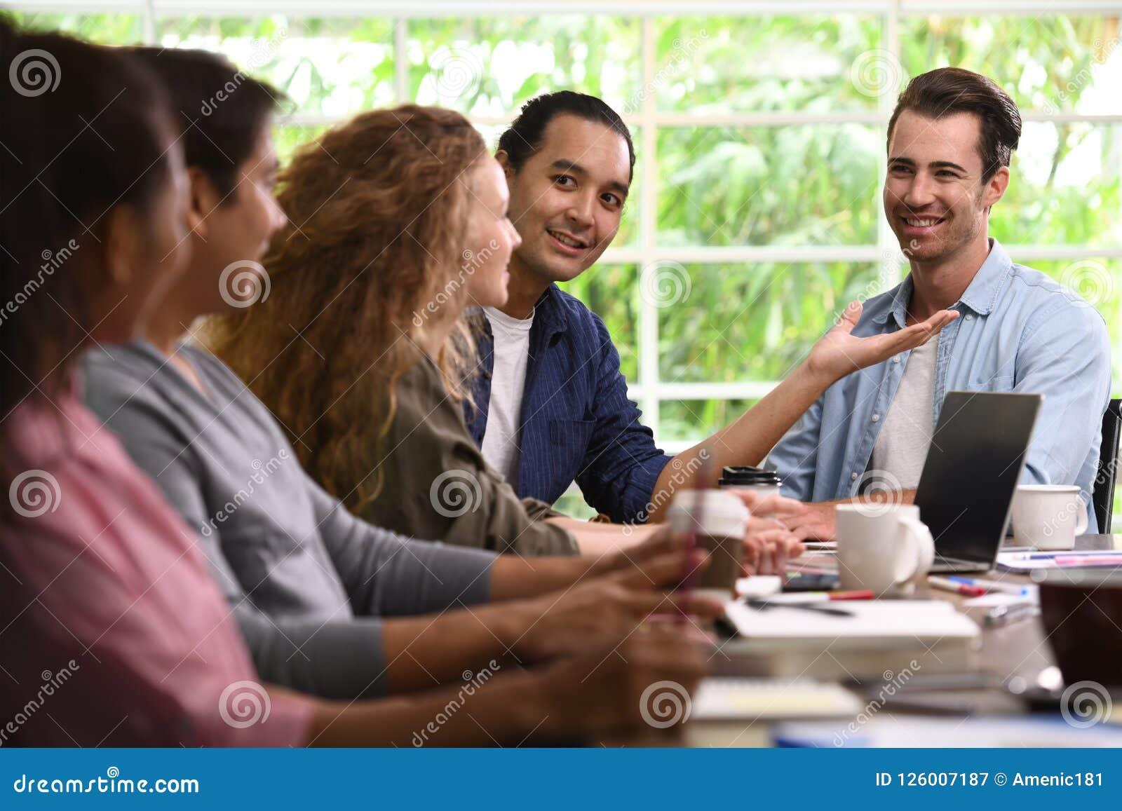Groep bedrijfspersonen in creatieve zaken die het werk in het bureau bespreken