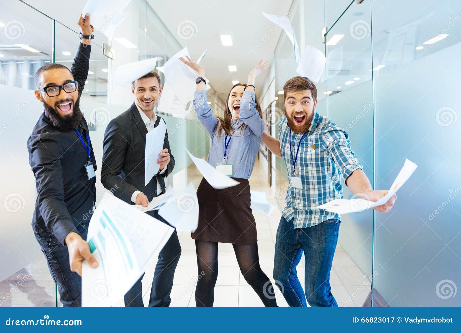 Groep blije opgewekte bedrijfsmensen die pret in bureau hebben