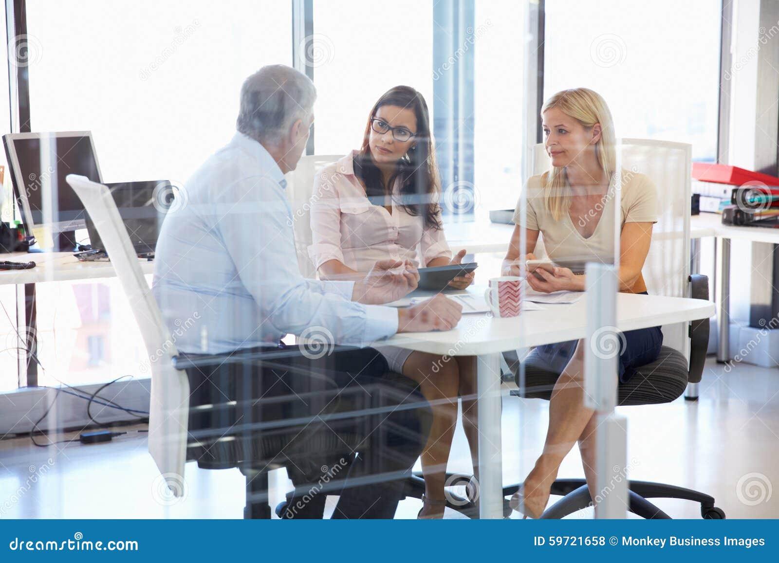Groep collega s die rond een lijst in een bureau samenkomen stock