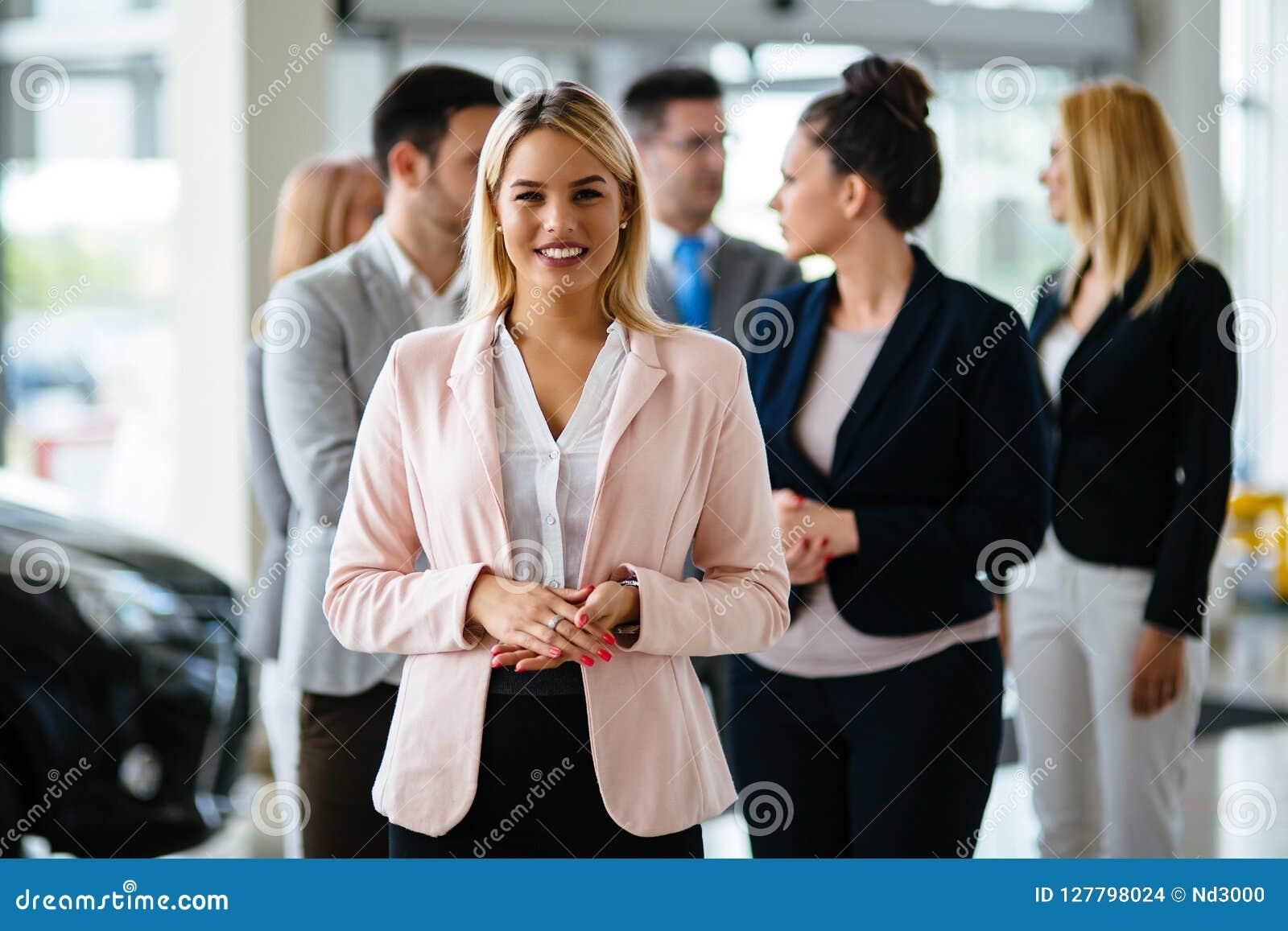 Groep de gelukkige adviseurs die van de autoverkoop binnen voertuigtoonzaal werken