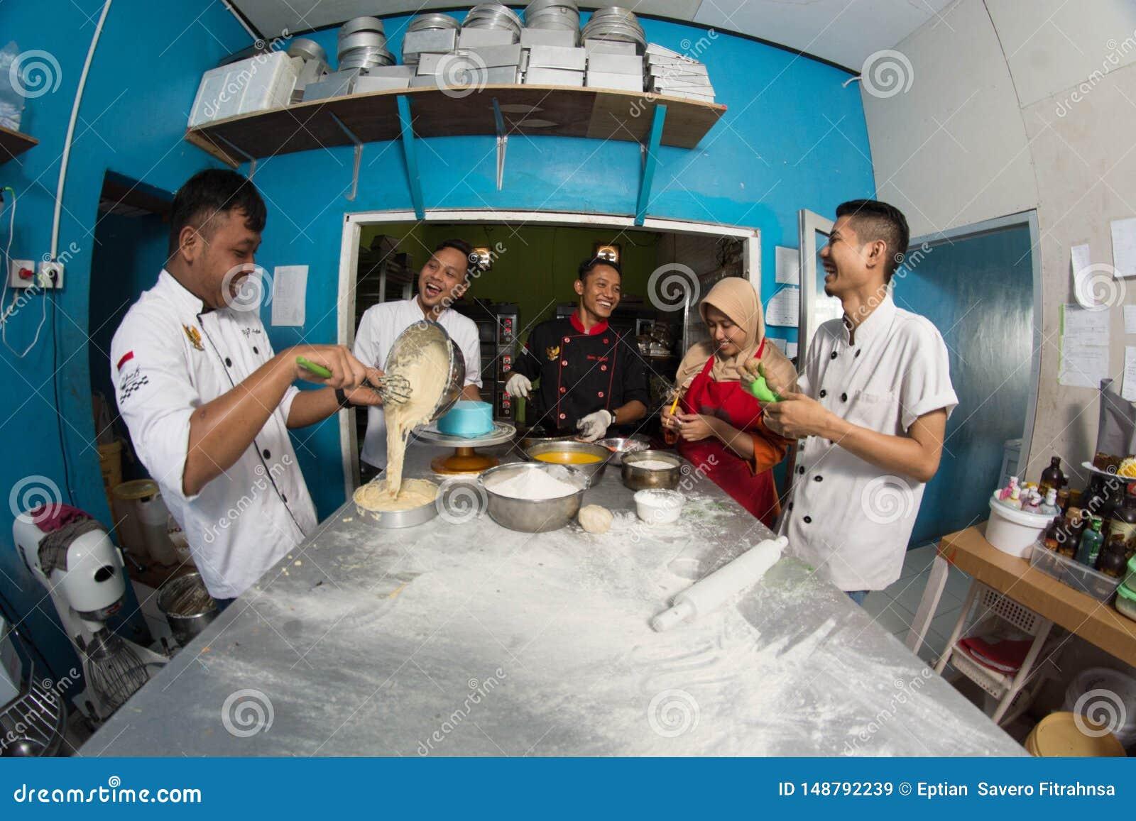Groep de gelukkige jonge Aziatische chef-kok die van de gebakjebakkerij deeg met bloem voorbereiden die binnen keuken werken
