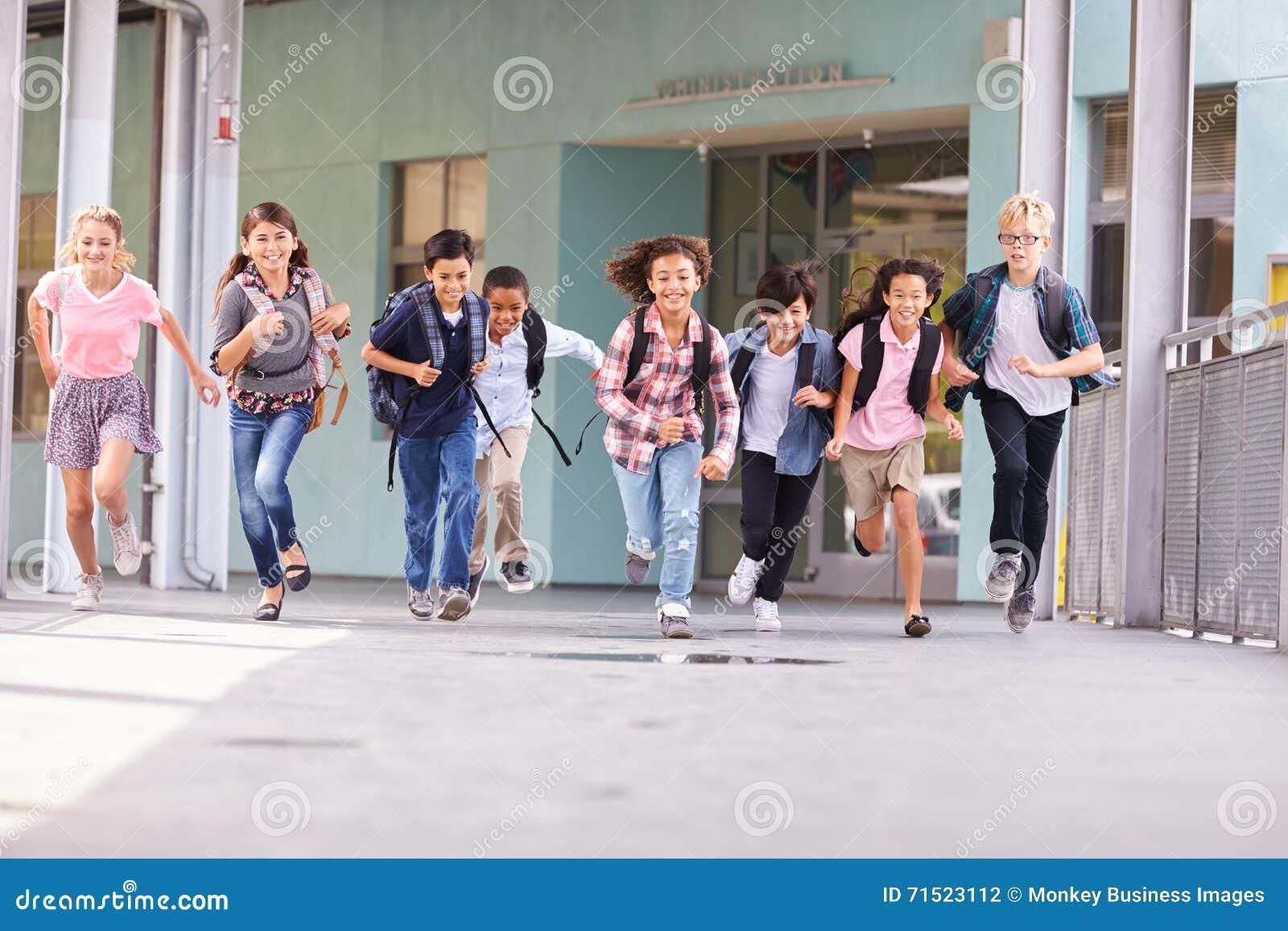 Groep die basisschooljonge geitjes in een schoolgang lopen