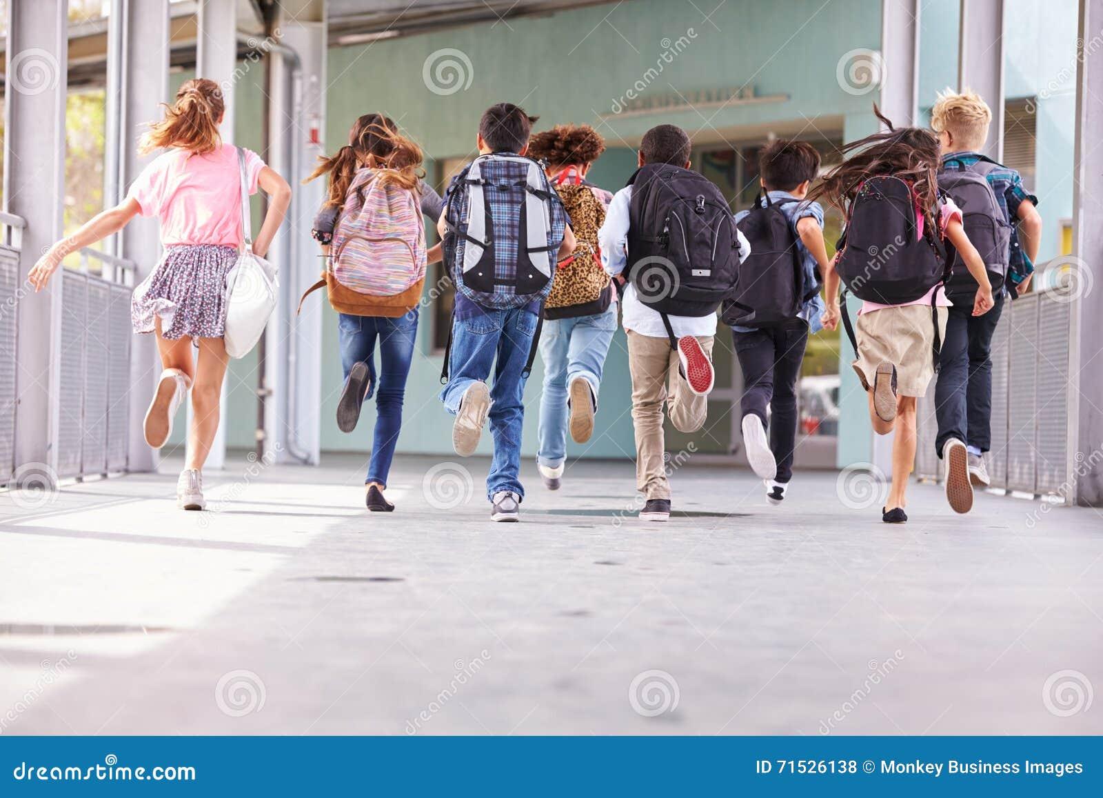 Groep die basisschooljonge geitjes op school, achtermening lopen