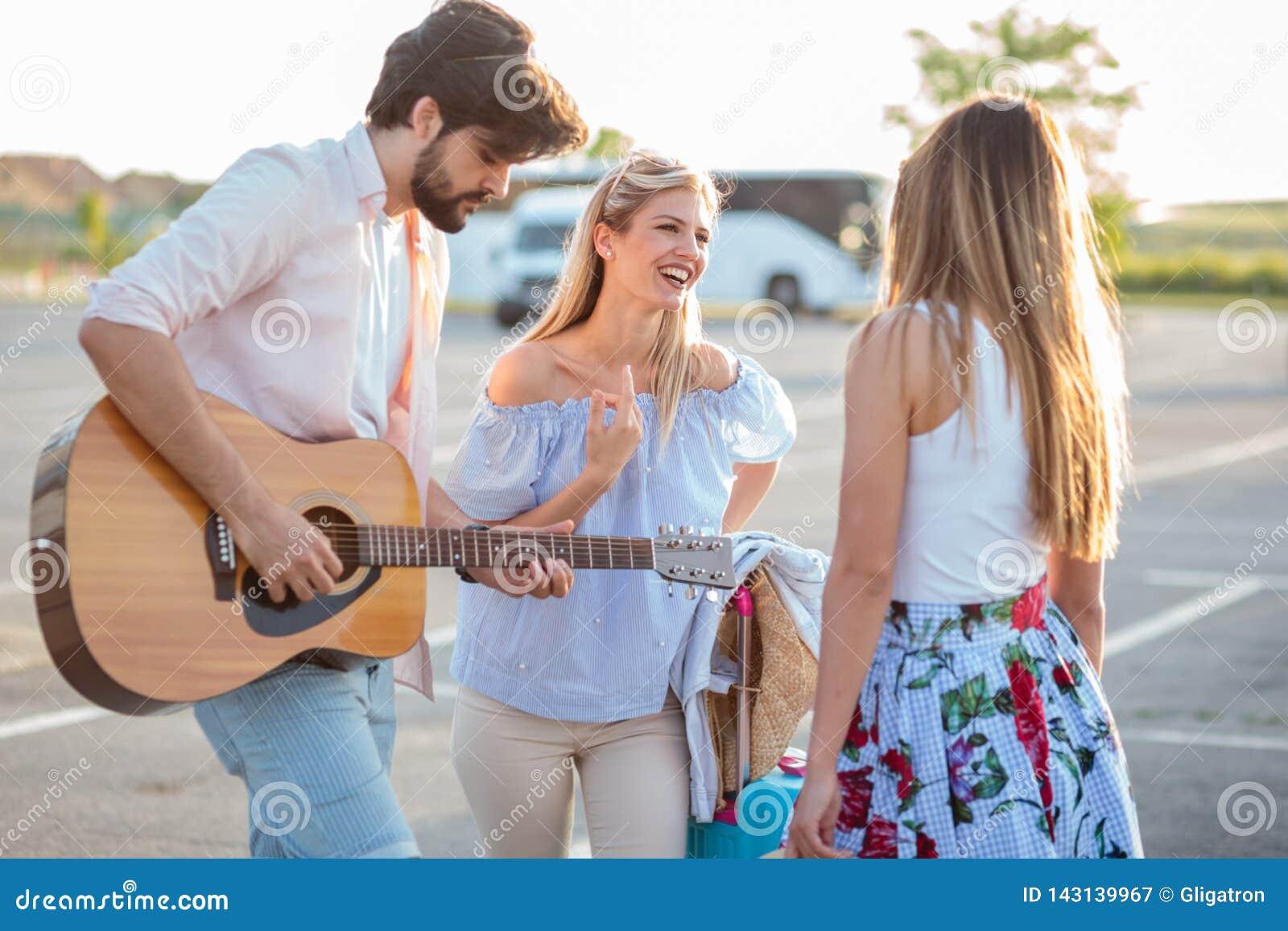 Groep die jonge toeristen die pret hebben en gitaar in een parkeerterrein spelen, op vervoer wachten