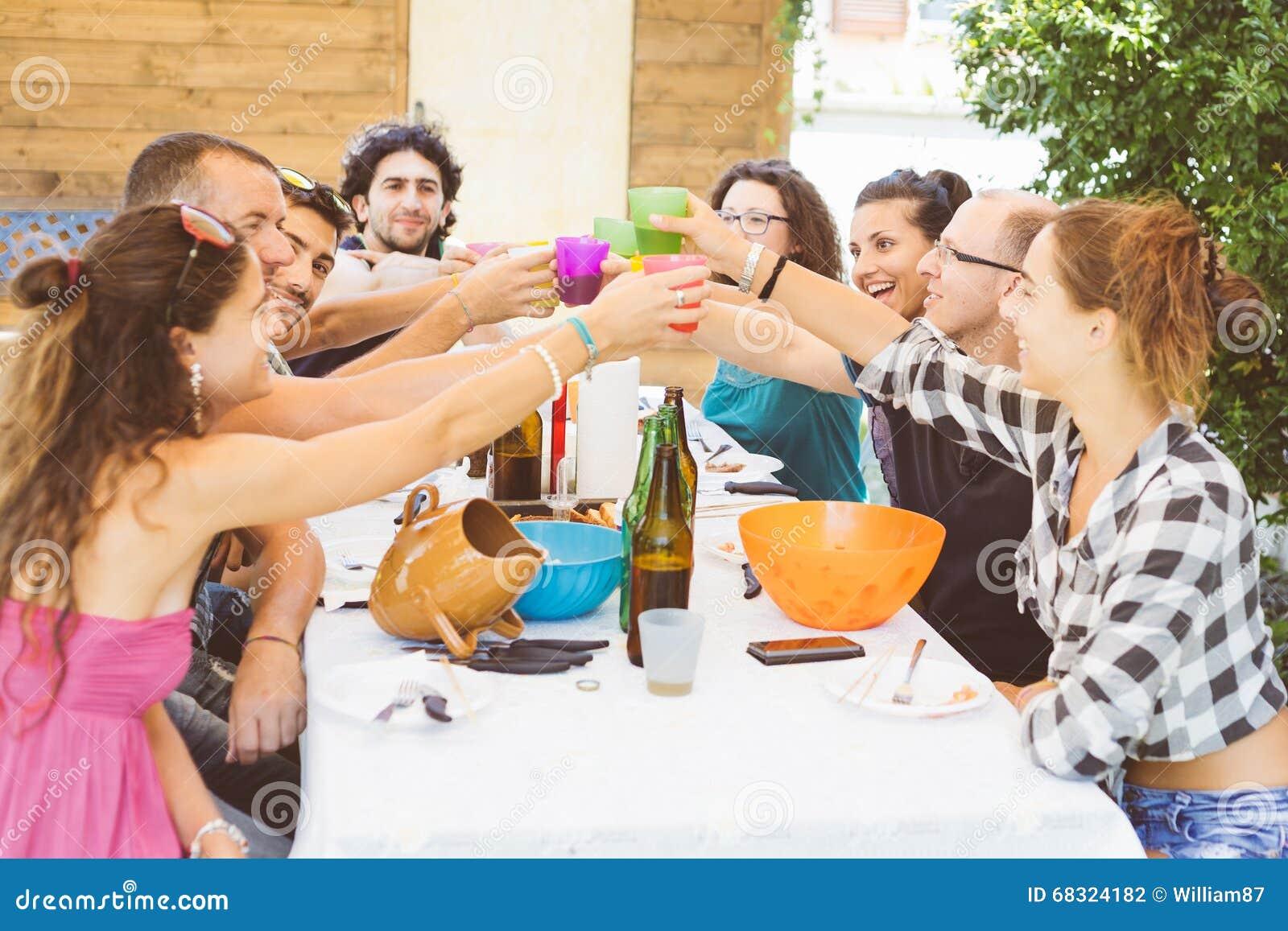 Groep die mensen hebbend lunch samen en roosterend zitten
