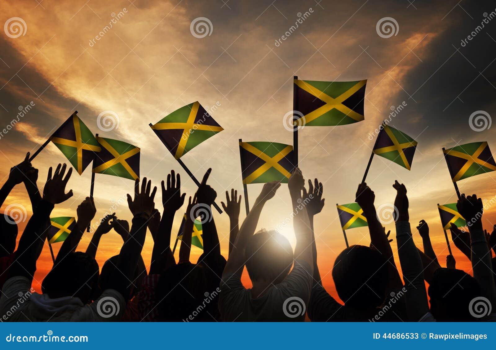 Groep die Mensen Vlag van Jamaïca in Achterlit golven