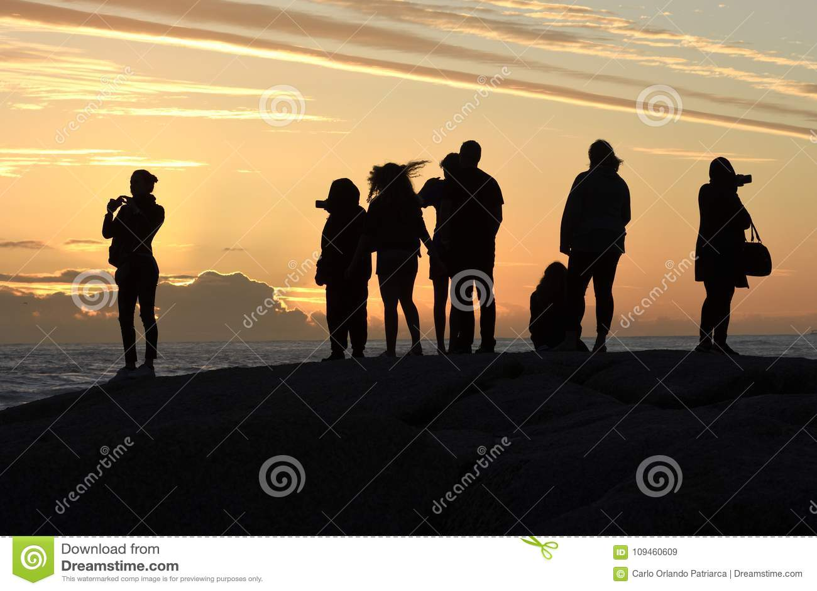 Groep die silhouetten op de zonsondergang in Kampenbaai letten, Cape Town, Zuid-Afrika