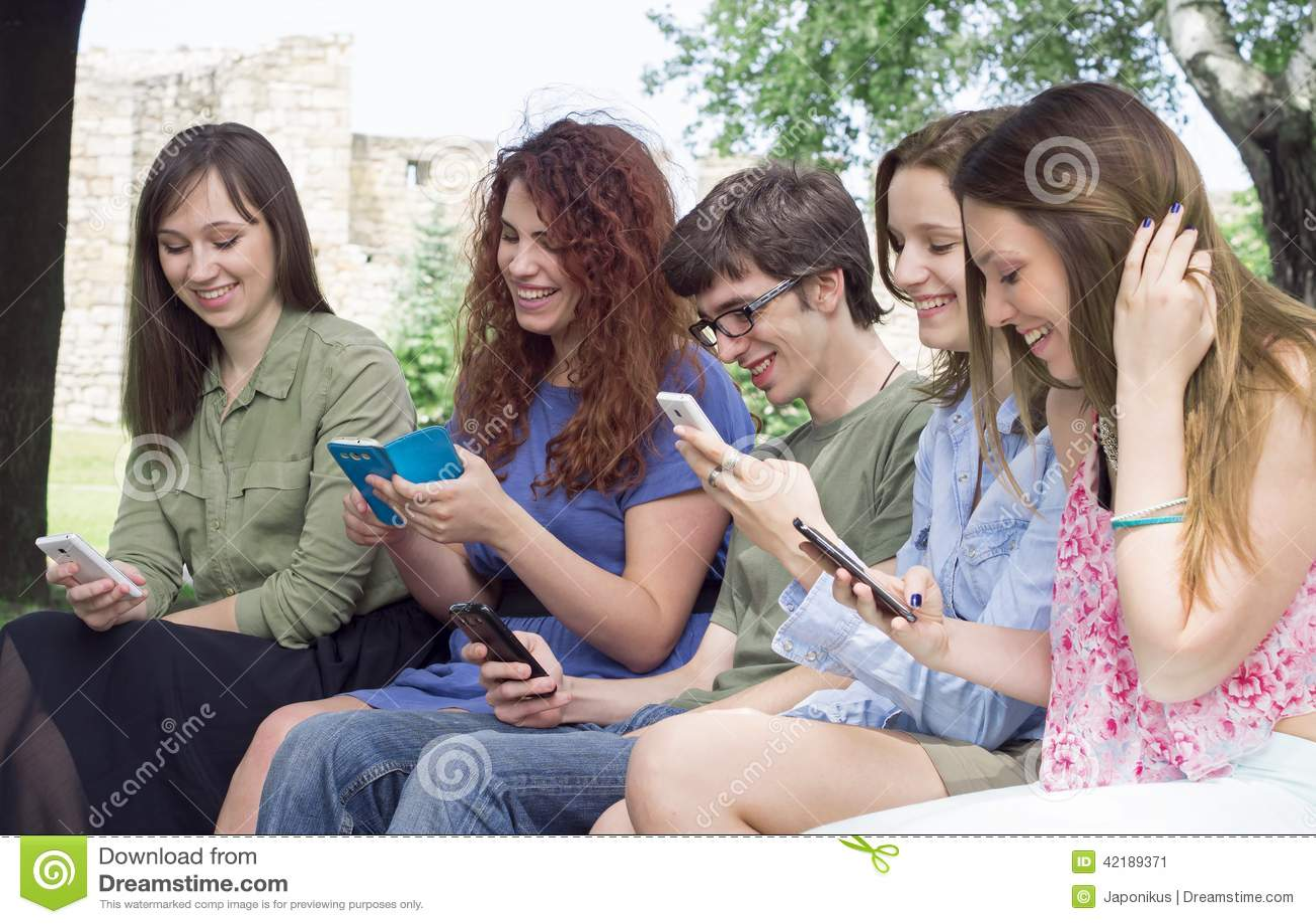 Groep gelukkige jonge studenten die mobiele telefoons i bekijken