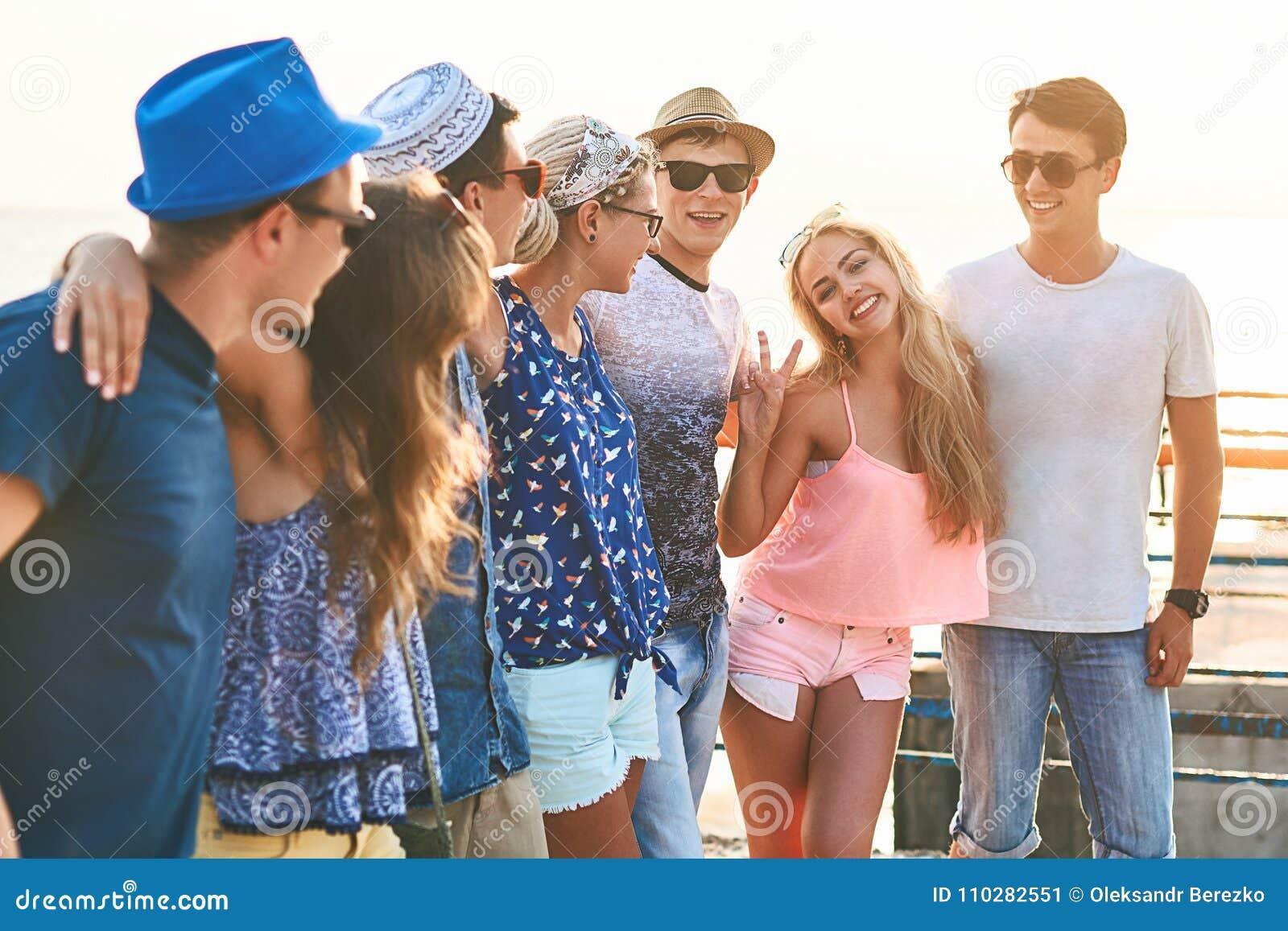 Groep gelukkige onbezorgde vrienden die uit bij de zonnige de zomerkust hangen