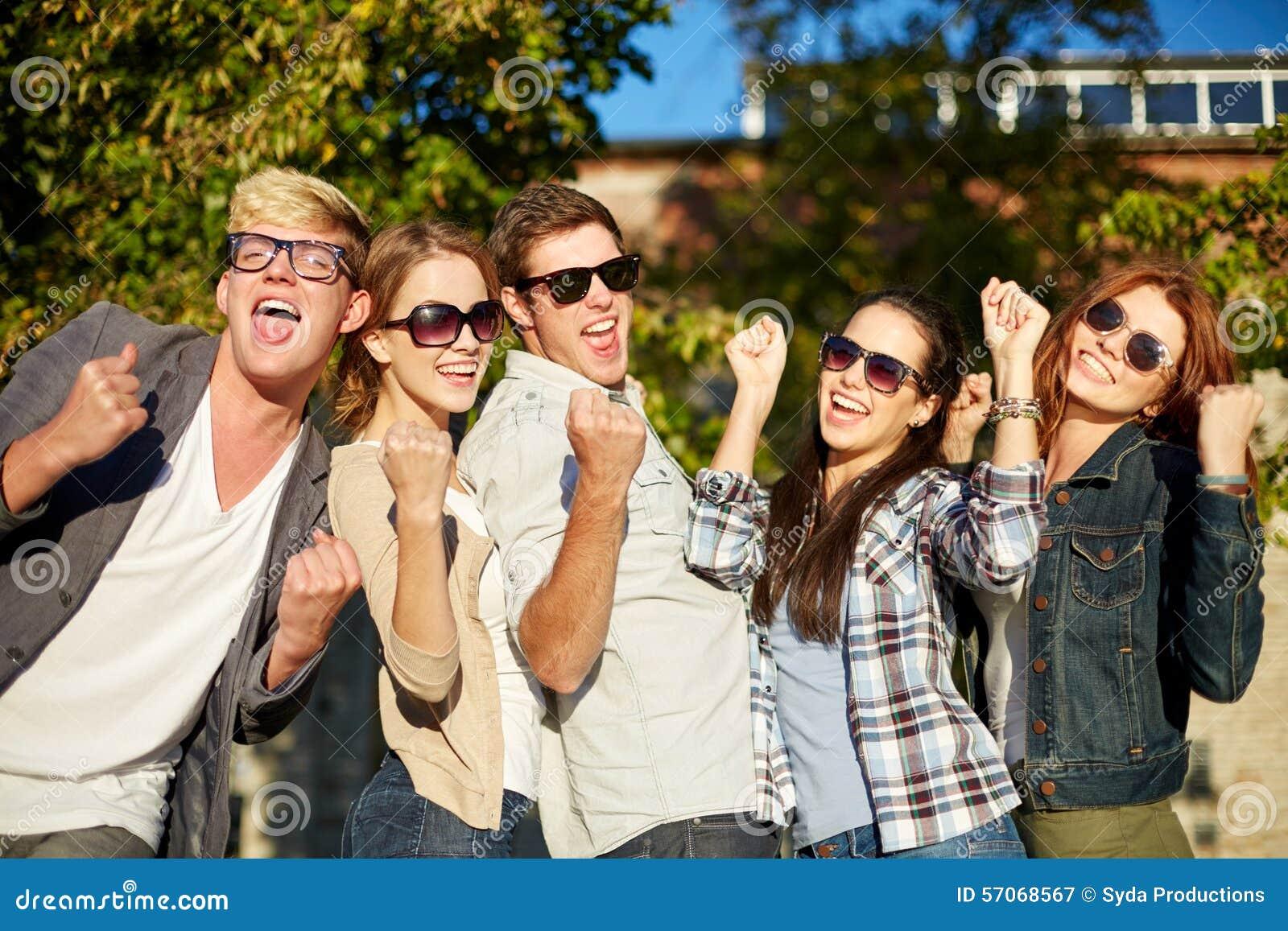 Groep gelukkige vrienden die triomfgebaar tonen