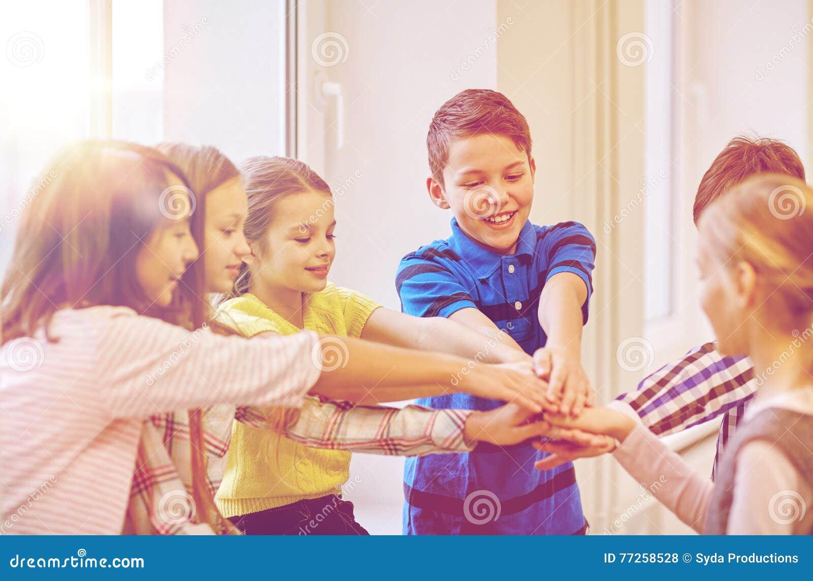 Groep het glimlachen van schooljonge geitjes die handen op bovenkant zetten