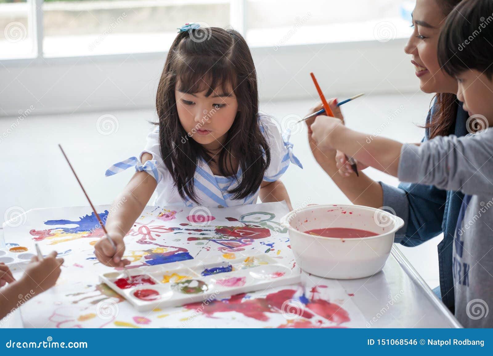 Groep het Leuke meisjestudent schilderen samen met kinderdagverblijfleraar in klaslokaalschool Gelukkige kinderen in een kleuters