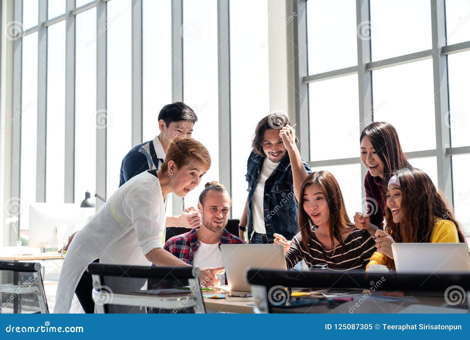 Groep het Team die van Diversiteitsmensen in het succeswerk met laptop op modern kantoor glimlachen en wordt opgewekt