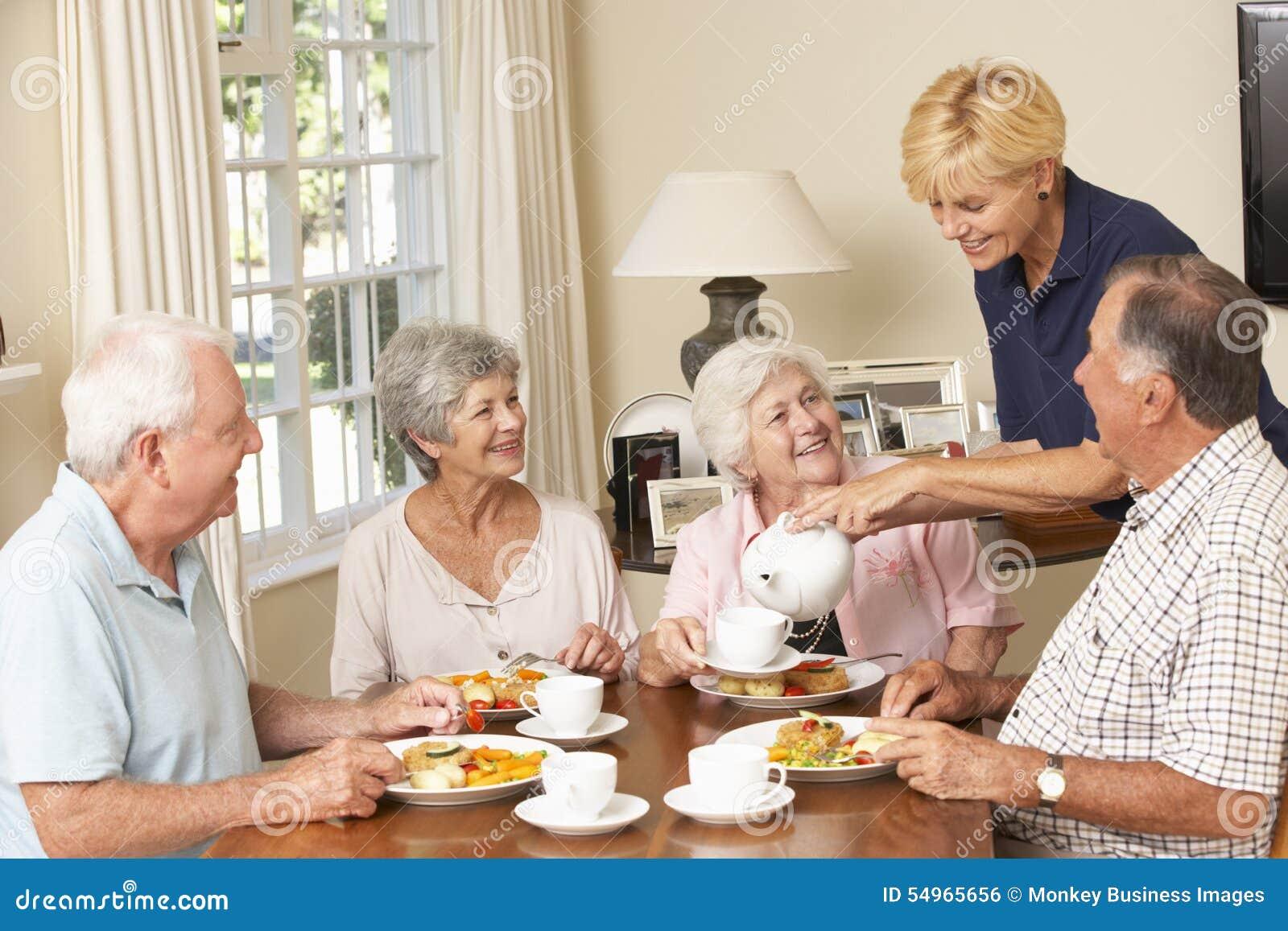 Groep Hogere Paren die van Maaltijd samen in Zorghuis genieten met Huishulp