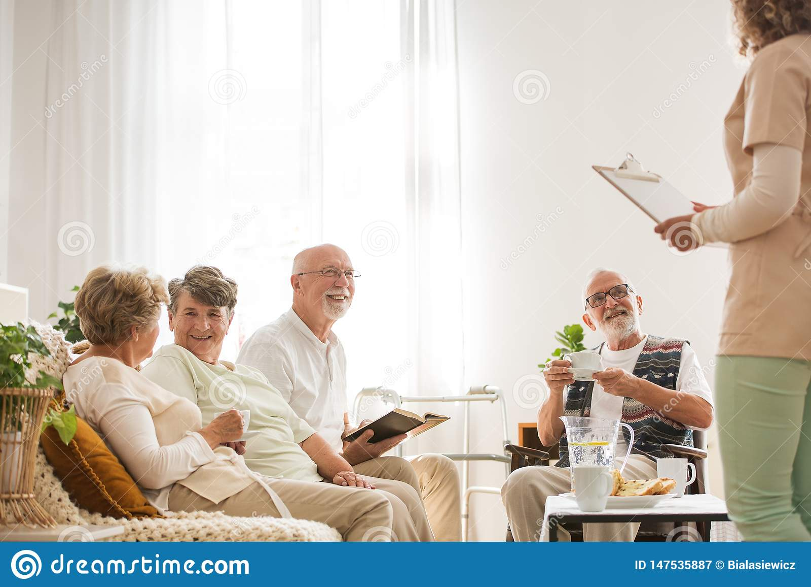 Groep hogere verpleeghuisgepensioneerden die samen bij gemeenschappelijke woonkamer zitten die aan jonge verpleegster luisteren