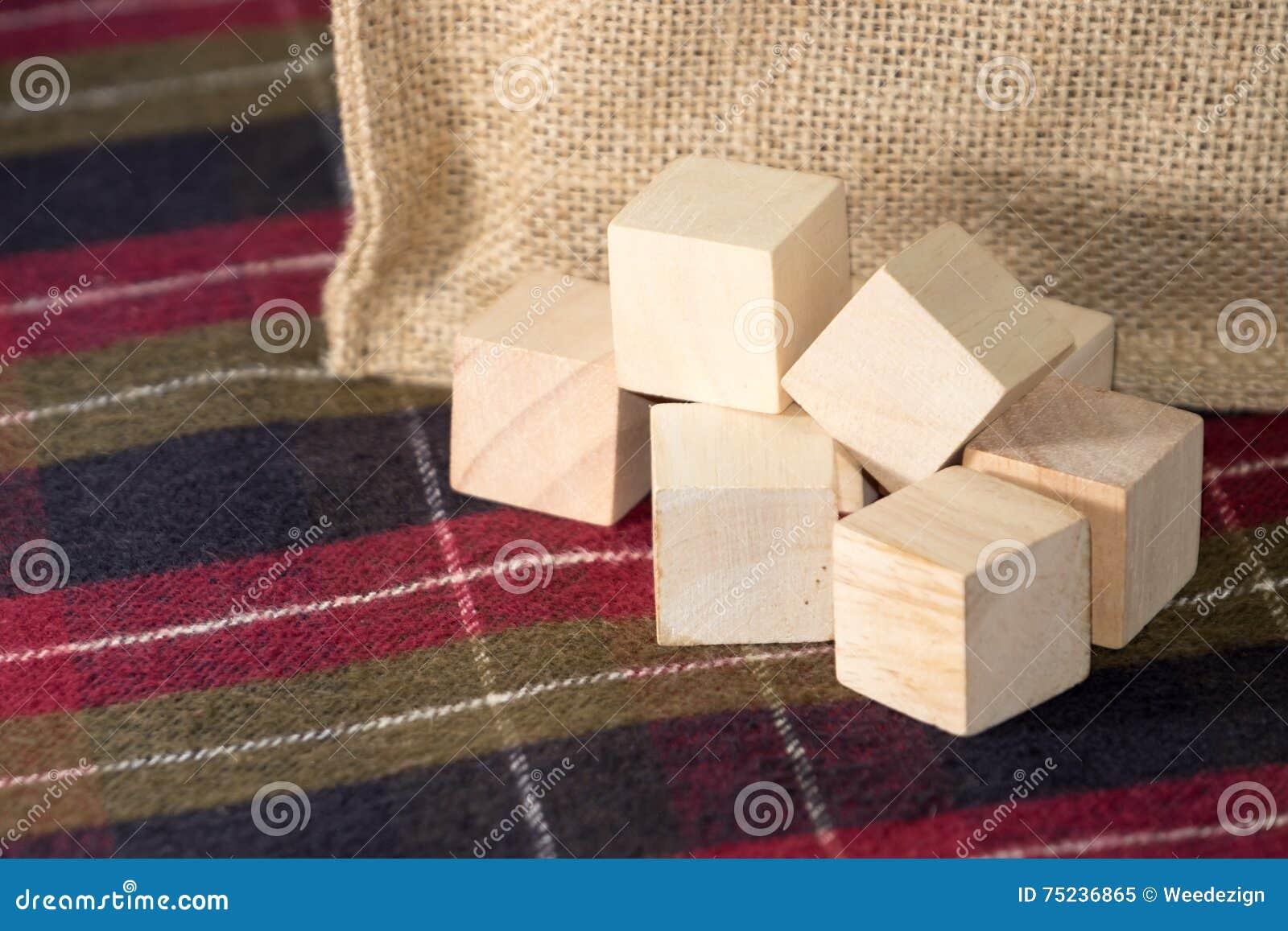 Groep houten kubus op geruit patroontafelkleed met zak bij