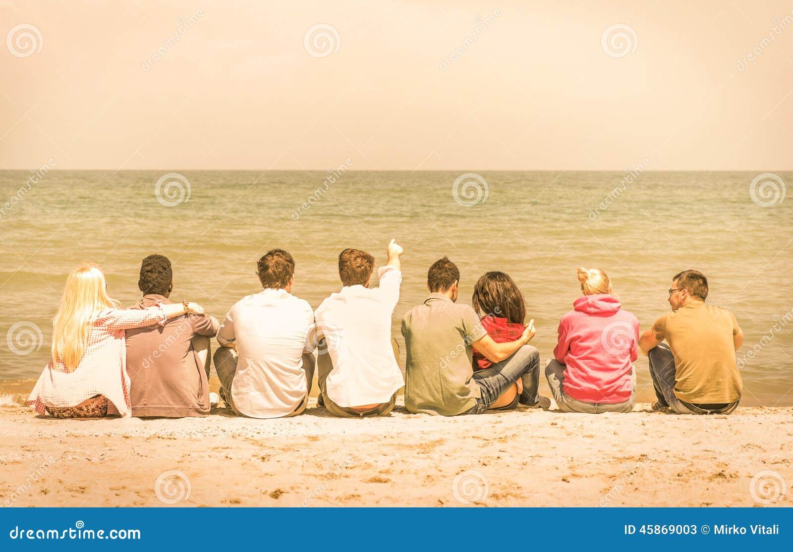Groep internationale multiraciale vrienden die bij het strand zitten