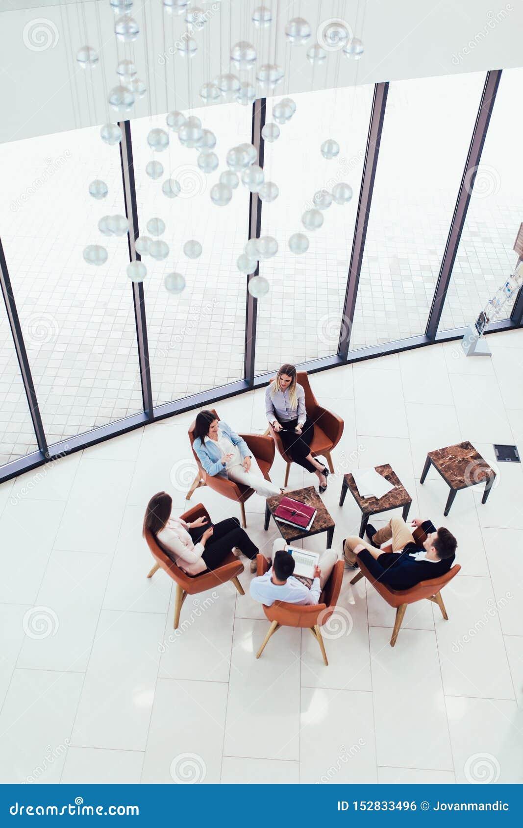 Groep jonge bedrijfsberoeps die samen en het toevallige bespreken in bureaugang het bereiken doelstellingen zitten hebben