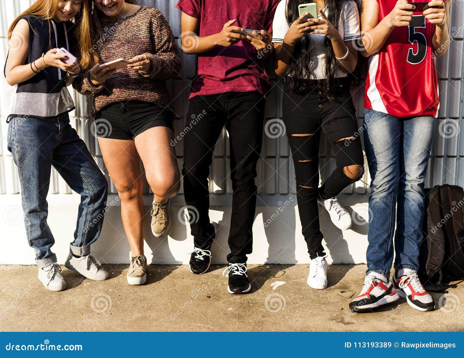 Groep jonge tienervrienden die samen uit het hanteren van smartphone sociaal media concept koelen
