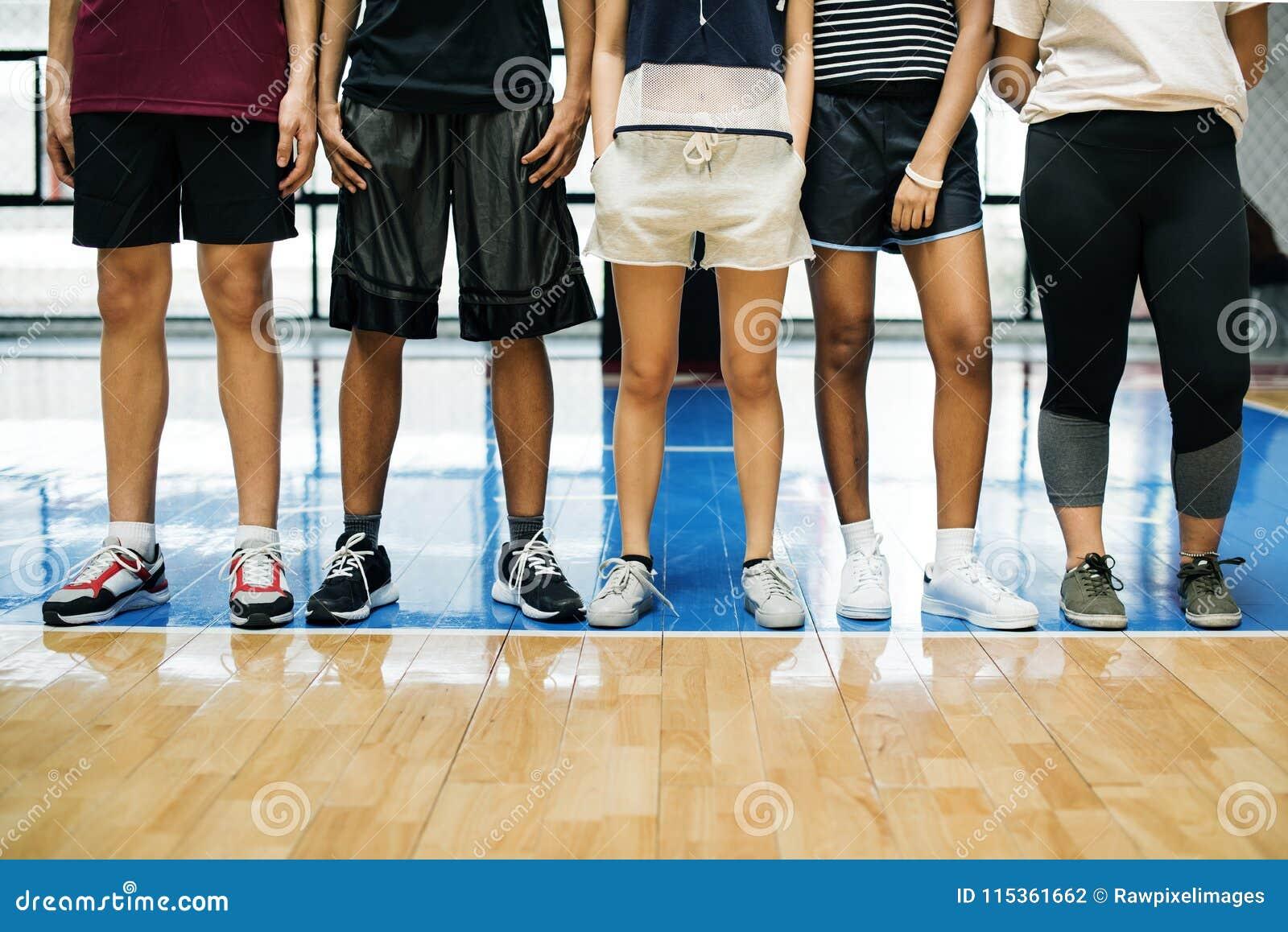 Groep jonge tienervrienden op een basketbalhof die zich op een rij bevinden