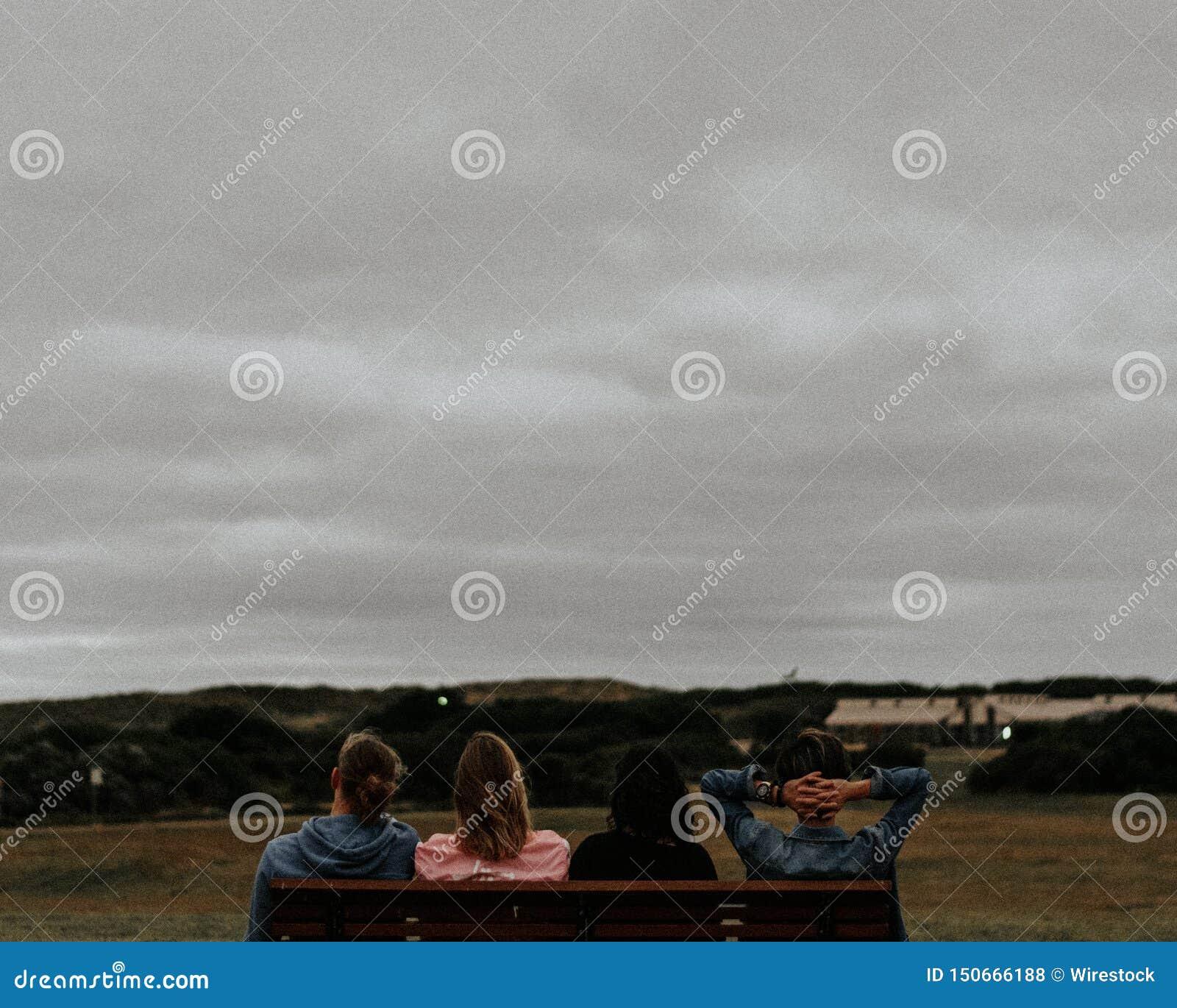 Groep jonge volwassenen die op een bank zitten en van de mening van oriëntatiepunten en grijze hemel genieten
