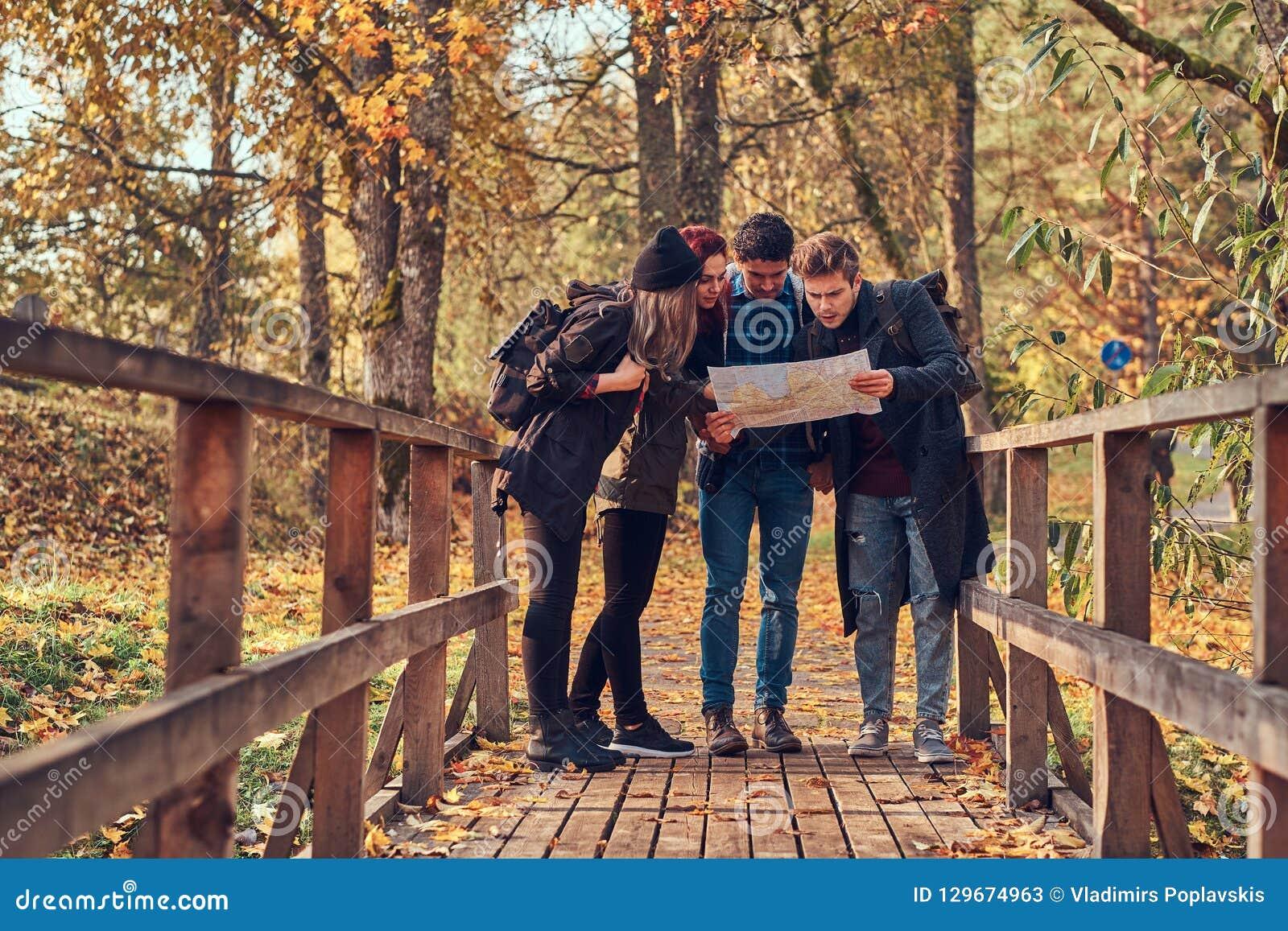 Groep jonge vrienden die in de herfst kleurrijk bos wandelen, bekijkend kaart en planningsstijging