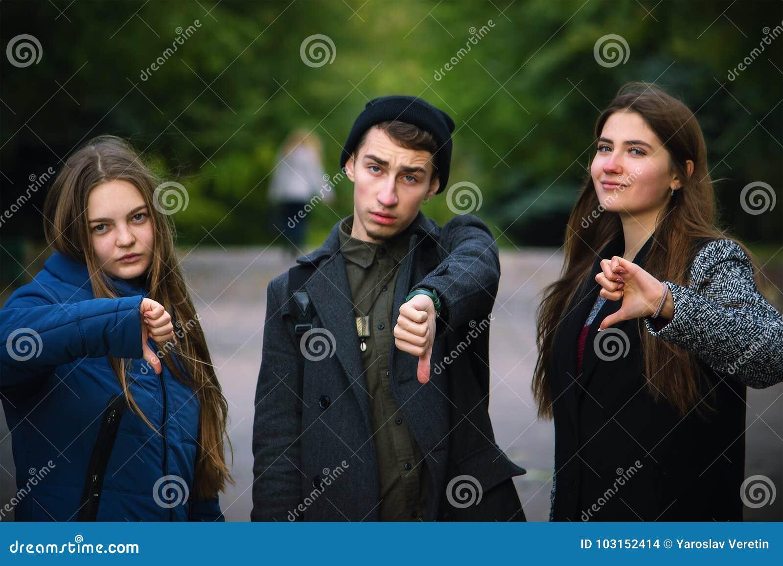 Groep jonge vrienden die duim neer tonen