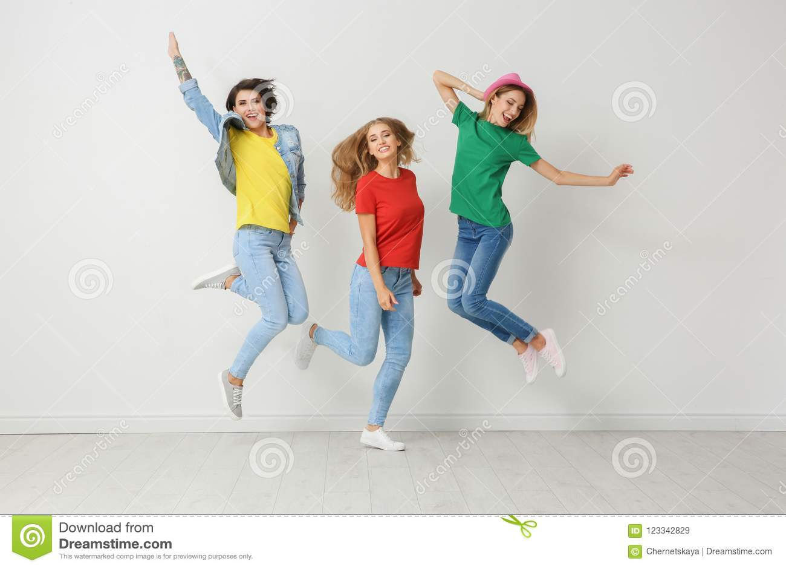 Groep jonge vrouwen in jeans en kleurrijke t-shirts