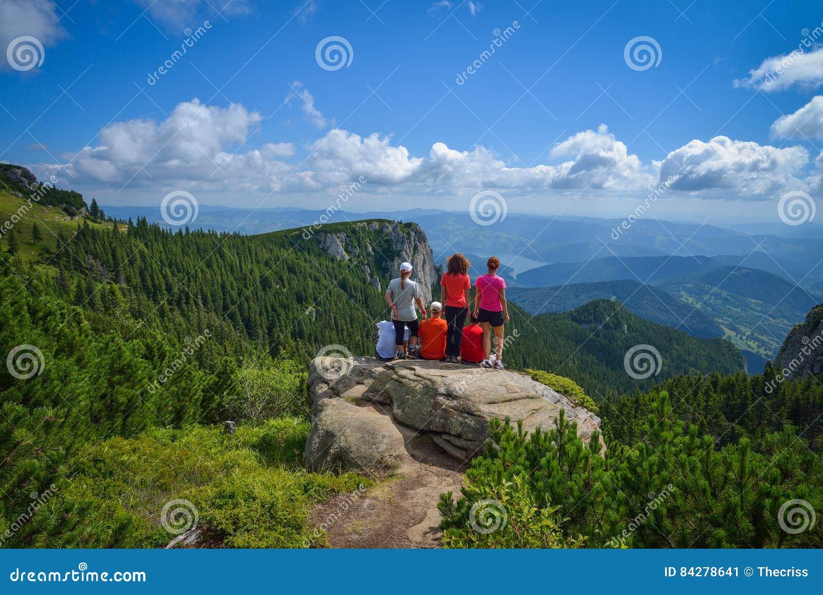 Groep jonge wandelaars die op een klippenrand zitten in de Ceahlau-bergen in Roemenië