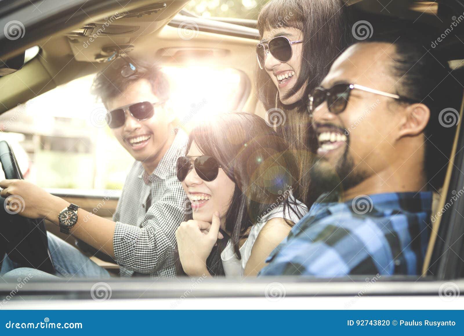 Groep jongeren die in auto glimlachen