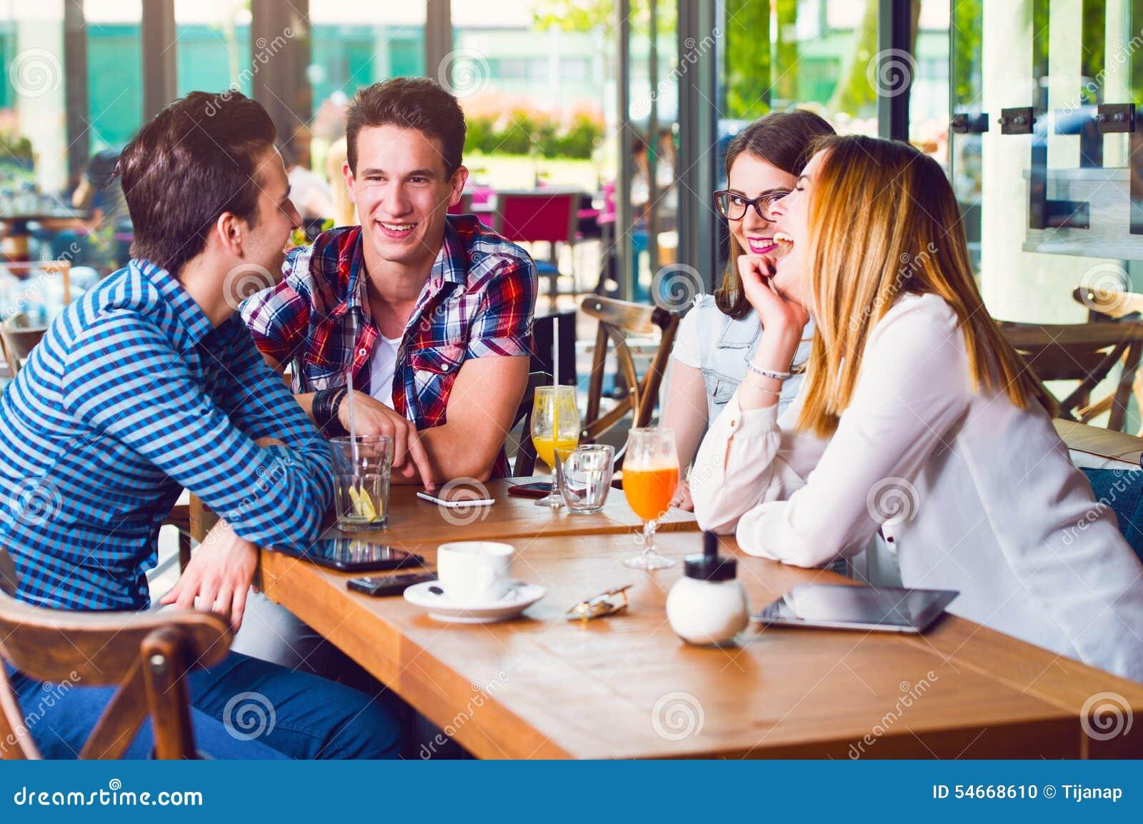 Groep jongeren die bij een koffie, het spreken en het genieten zitten van