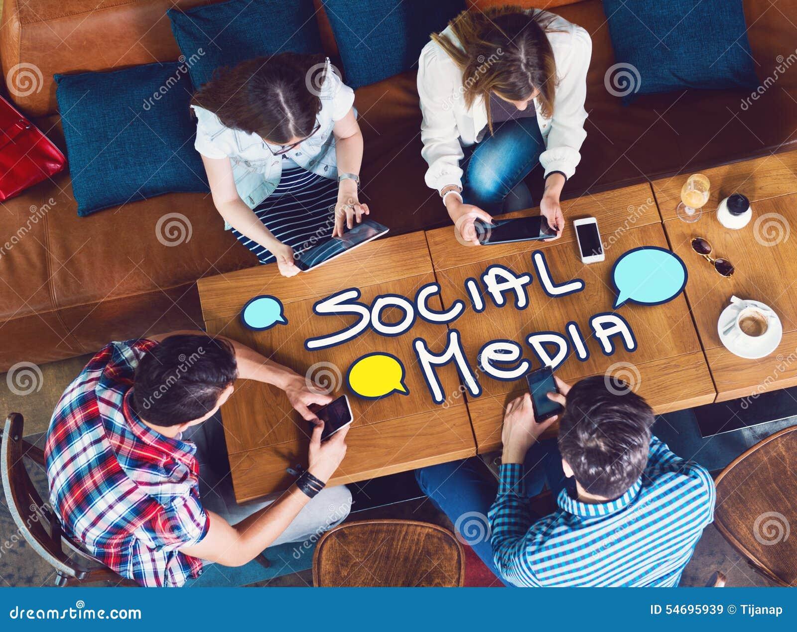 Groep jongeren die bij een koffie, met mobiles en tabletten zitten