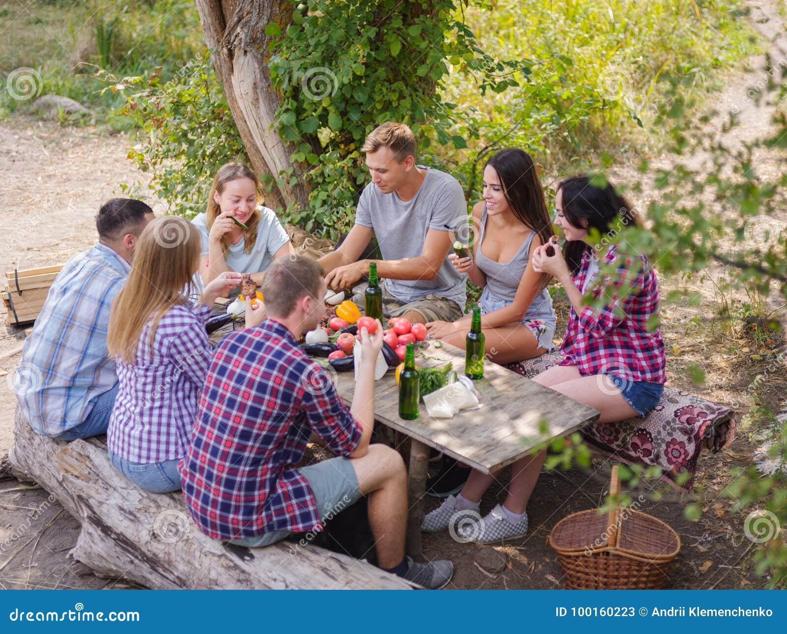 Groep jongeren die een rond lijst buiten zitten Zij genieten van om bieren te babbelen en te drinken