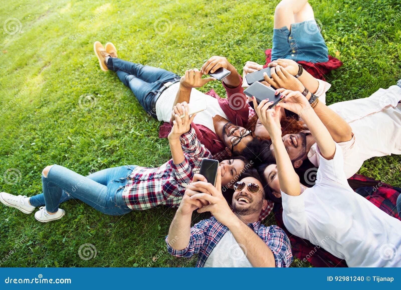 Groep jongeren die op het gras in cirkel, duimen leggen upGroup van jongeren die op het gras in cirkel leggen, die telefoons met